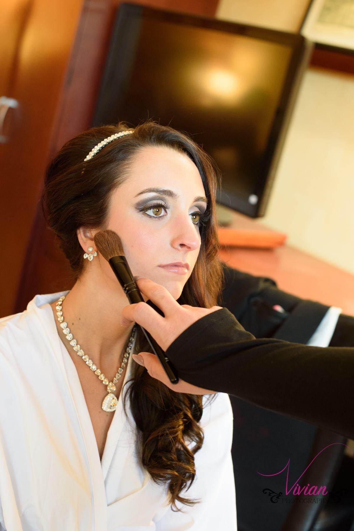 bride-getting-makeup-done-in-robe.jpg