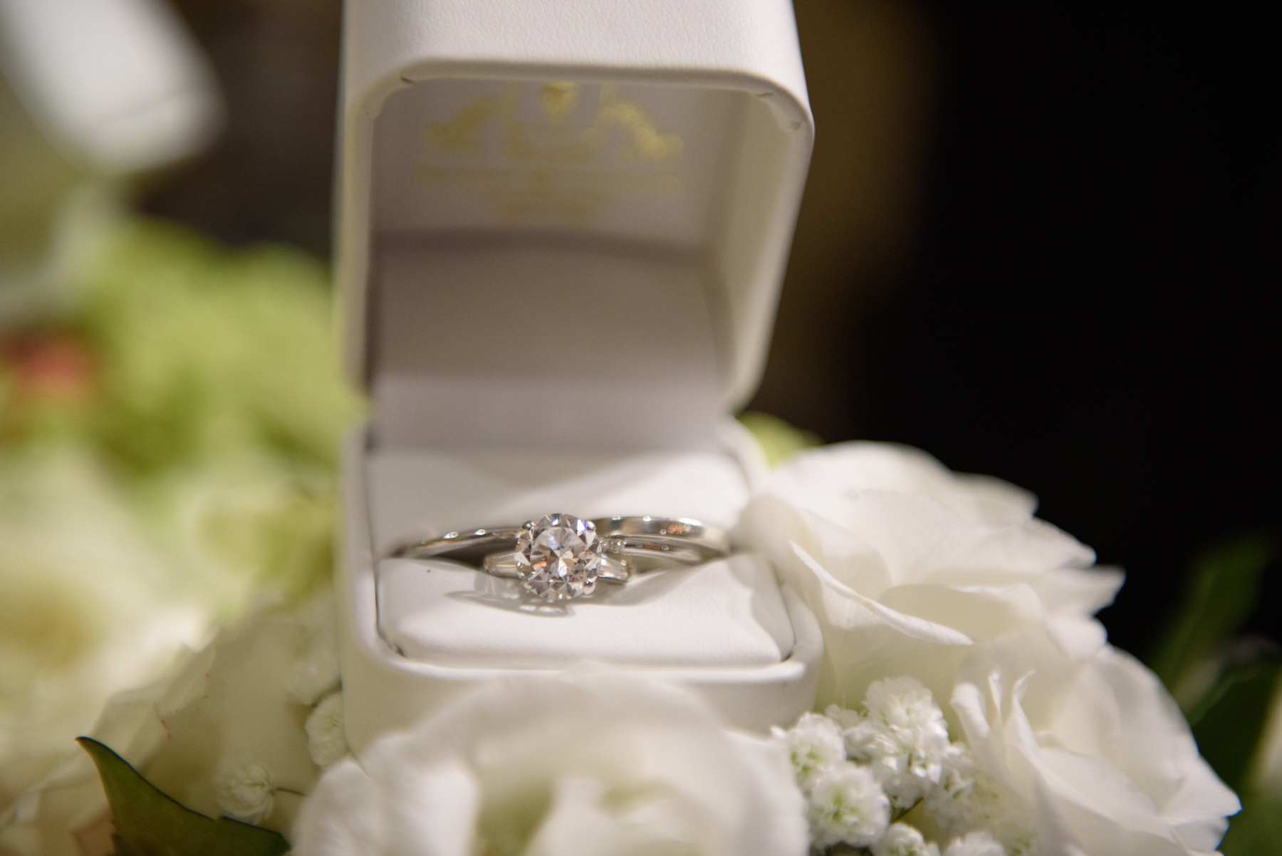 diamond-ring-sitting-in-white-box-on-flowers