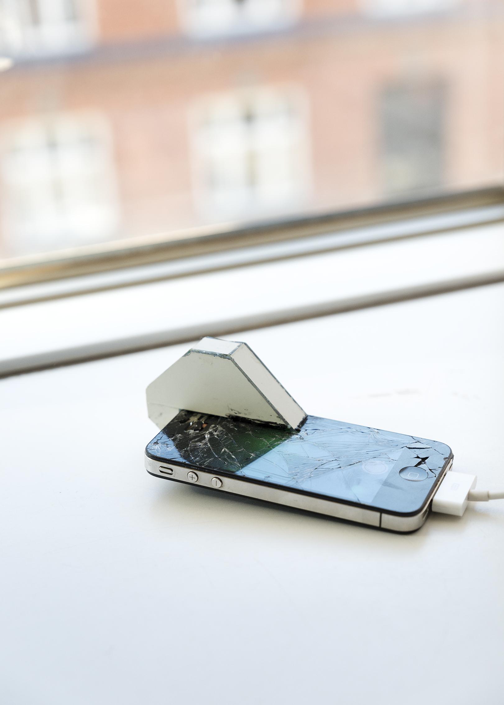 På radion talar de om ett hål i jorden (europium, europium, terbium)  (2015) Karl Isakson                        En sprucken skärm, speglar, en modifierad iPhone 4S. Telefonens kamera tittar på skärmen genom ett antal speglar. Min skärm pulserar, kontrasten är hög, röd fosfor, blå fosfor och lite grönt. På radion säger en till en annan att riset inte växer.   On the radio they are talking about a hole in the earth (europium, europium, terbium)   (2015) Karl Isakson          A cracked screen, mirrors, a modified iPhone 4S. The phone's camera is facing the screen guided by a number of mirrors. My screen pulsates, the contrast is high, red phosphor, blue phosphor and a little green. On the radio one says to another that the rice doesn't grow.