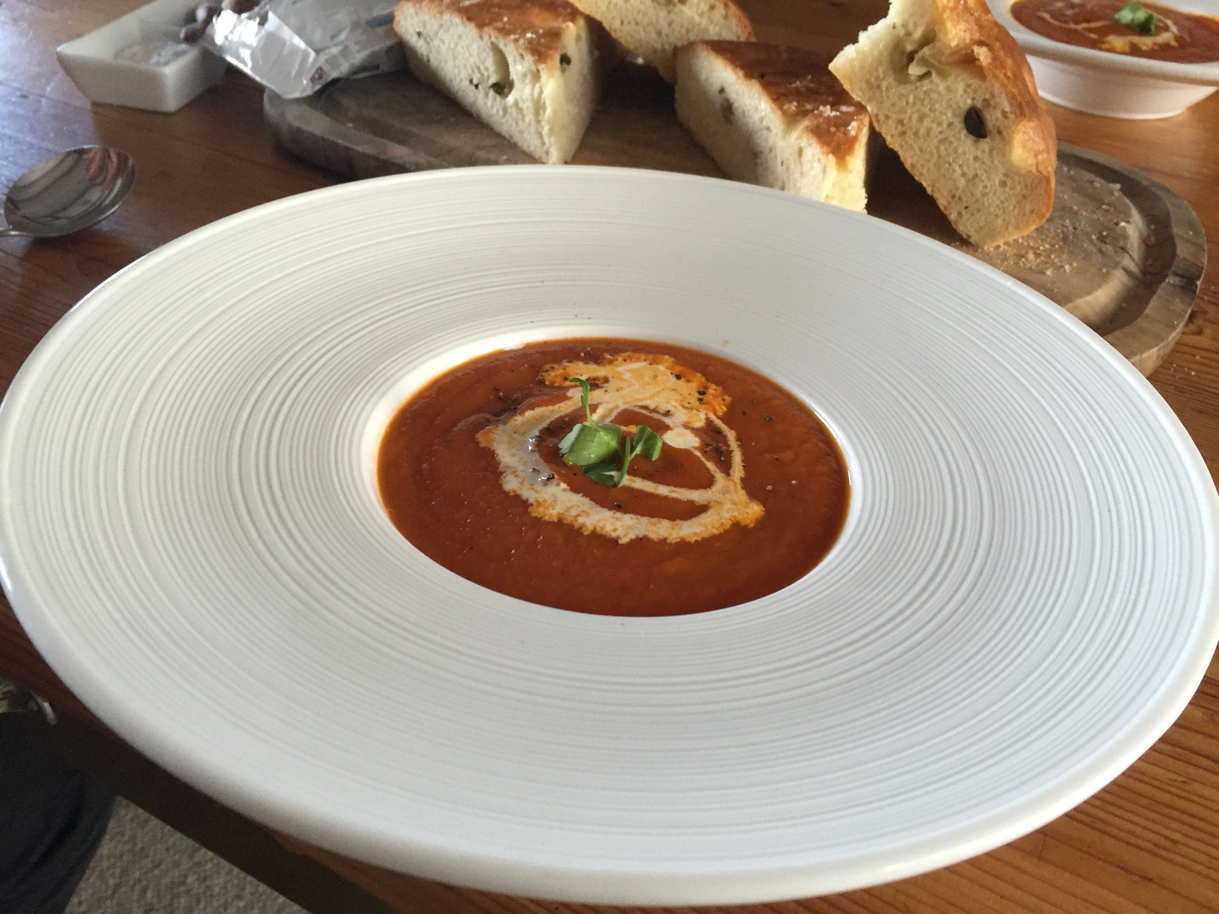 Roasted red pepper and tomato soup with creme fraiche and olive foccacia