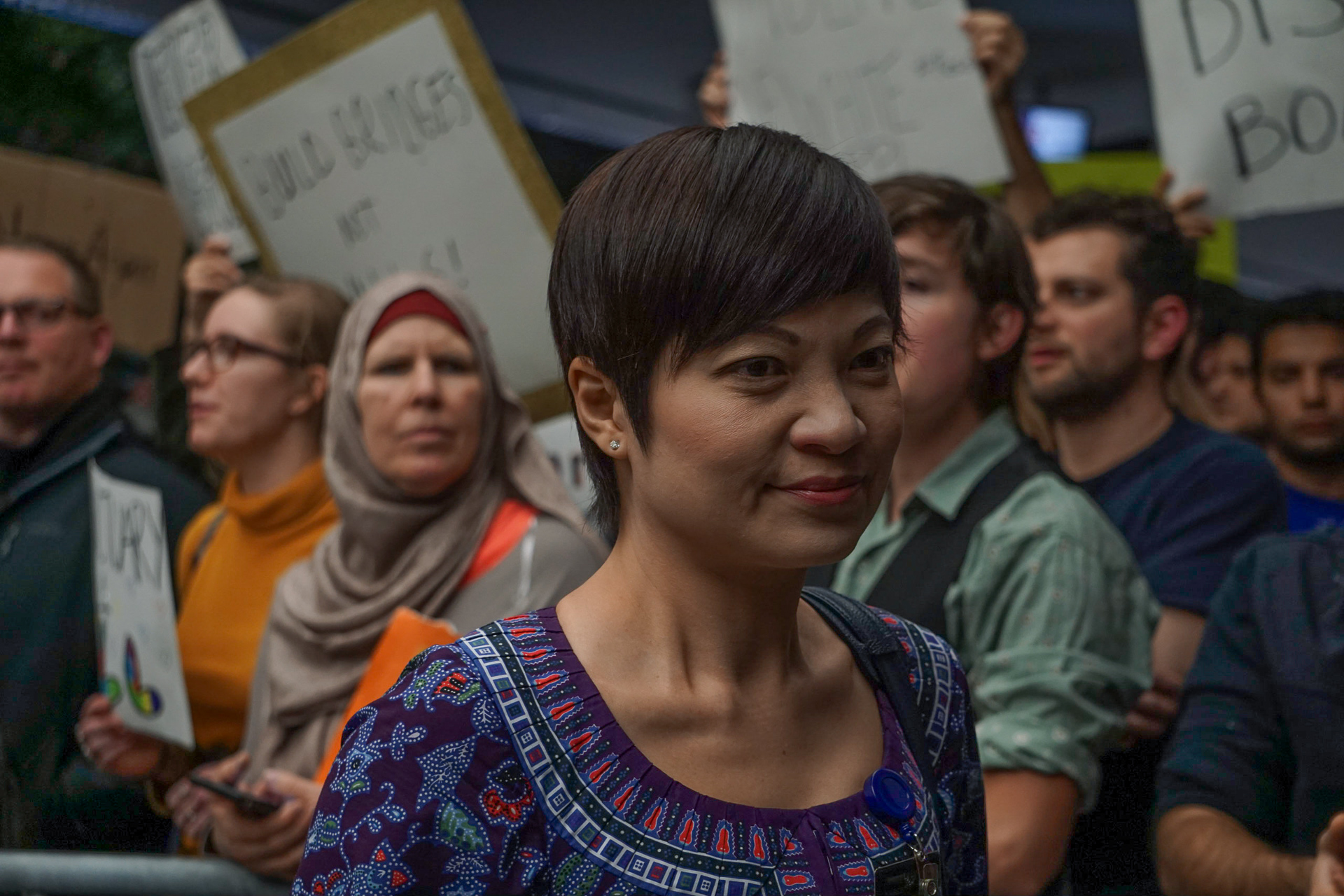 A woman exits the international terminal after arriving from over seas and is greeted by anti-Muslim Ban protestors welcoming her into the country.