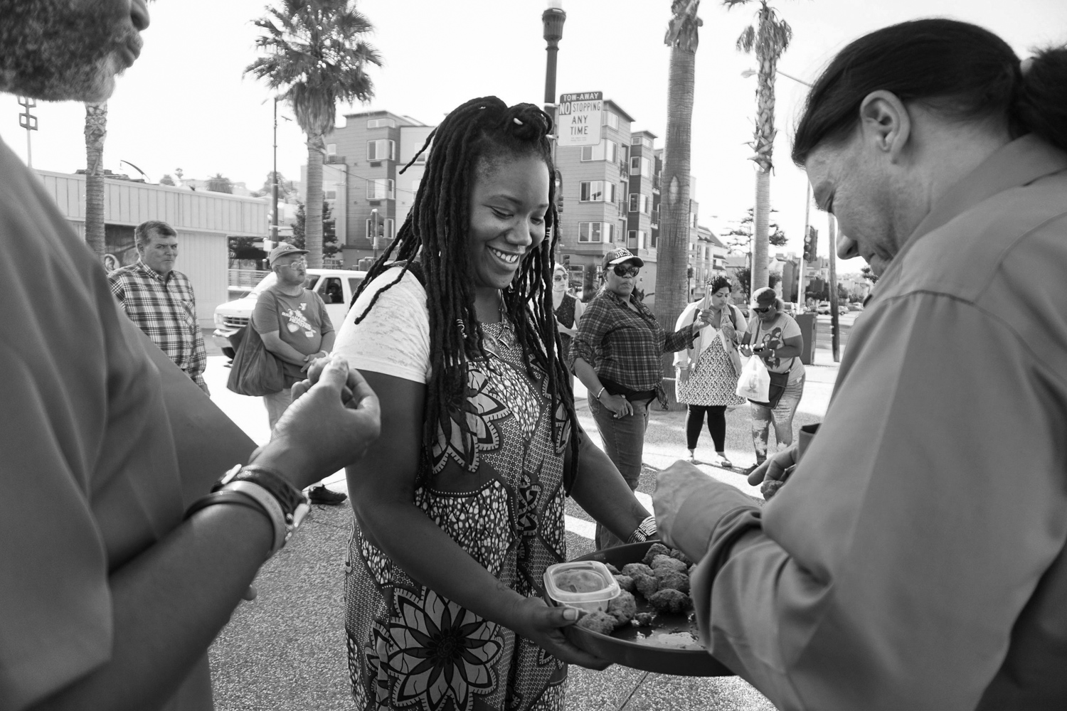 Aliyah Dunn-Salahudin passes out dumplings during a vigil to honor a young man shot by police 50 years ago.