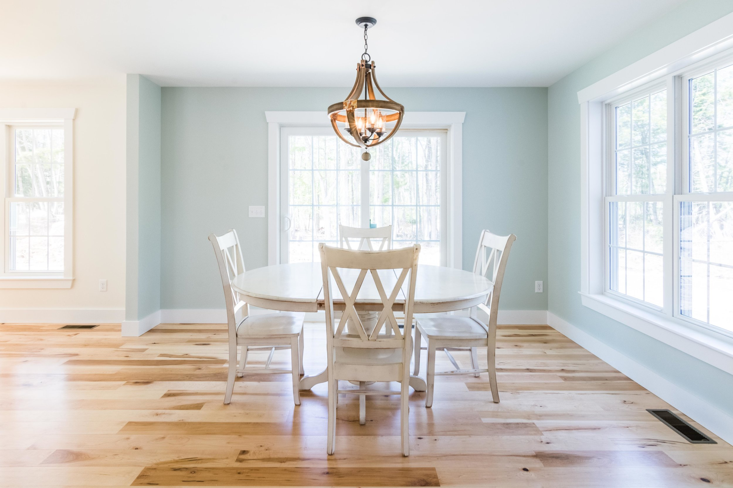 The dining area and living room flow into one another, forming a U shape around the staircase, delineated by a subtle change in wall color. The dining is painted with  Sea Salt  from Sherwin Williams, and the living is  Creamy , also from Sherwin Williams.