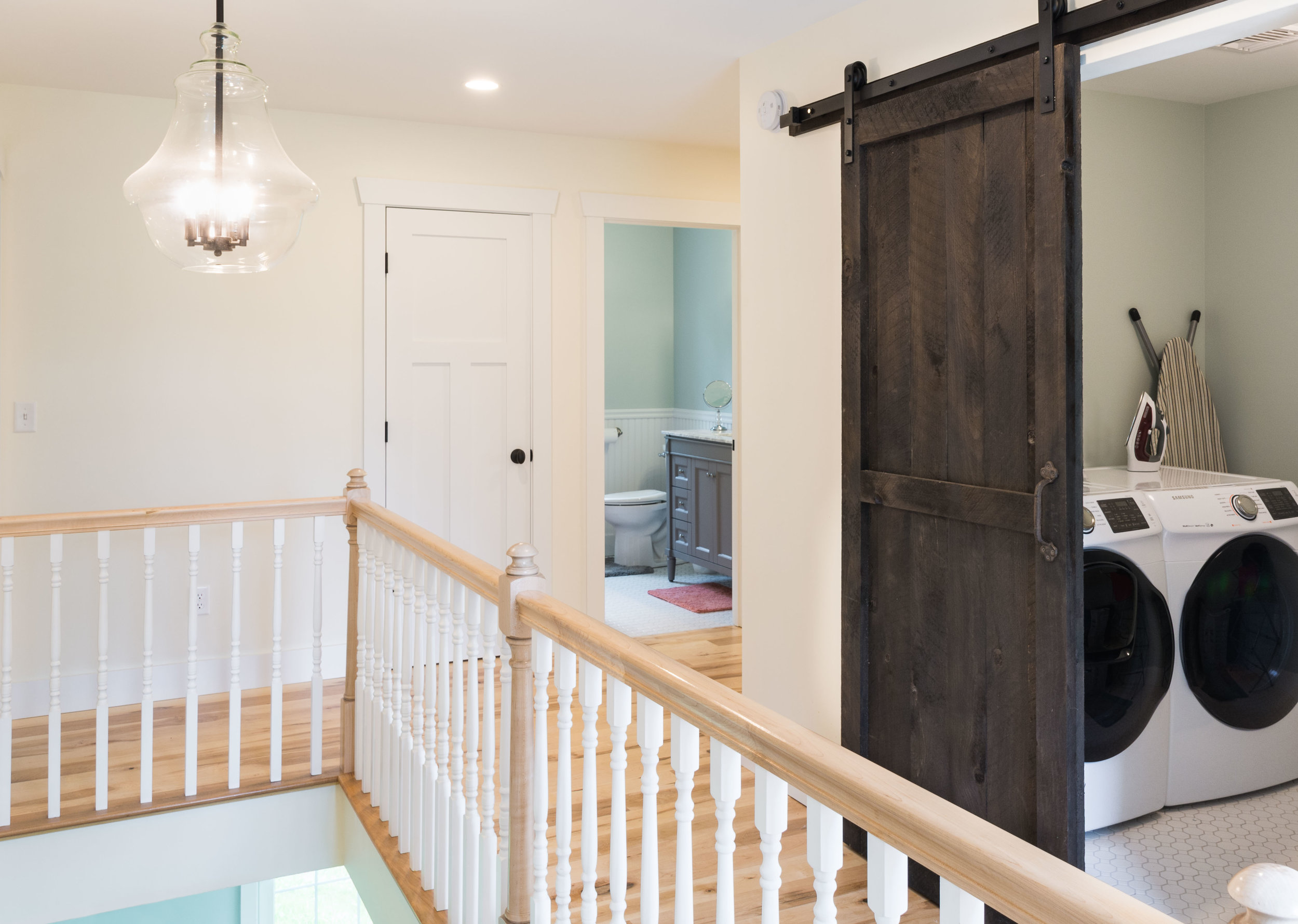 The upstairs laundry room can be hidden by a sliding barn door, stained in a dark walnut color and constructed by the homeowner.