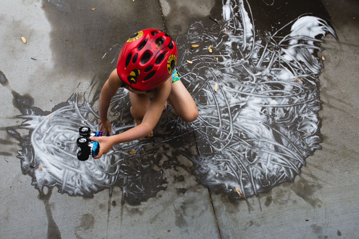 child in helmet playing with toy truck and bubbles
