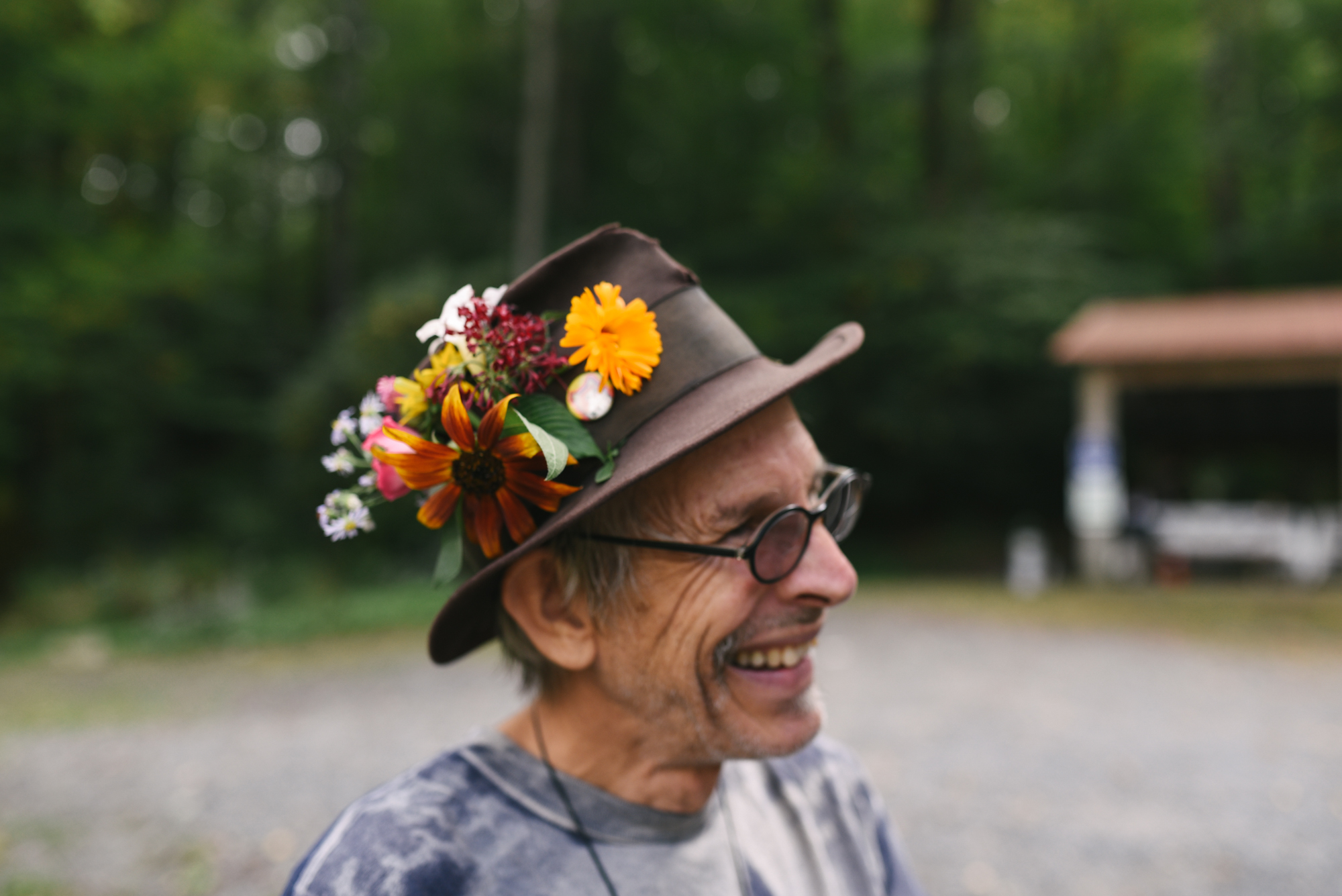 Mountain Wedding, Outdoors, Rustic, West Virginia, Maryland Wedding Photographer, DIY, Casual, Wedding Guest with flowers in his hat, guest smiling and laughing
