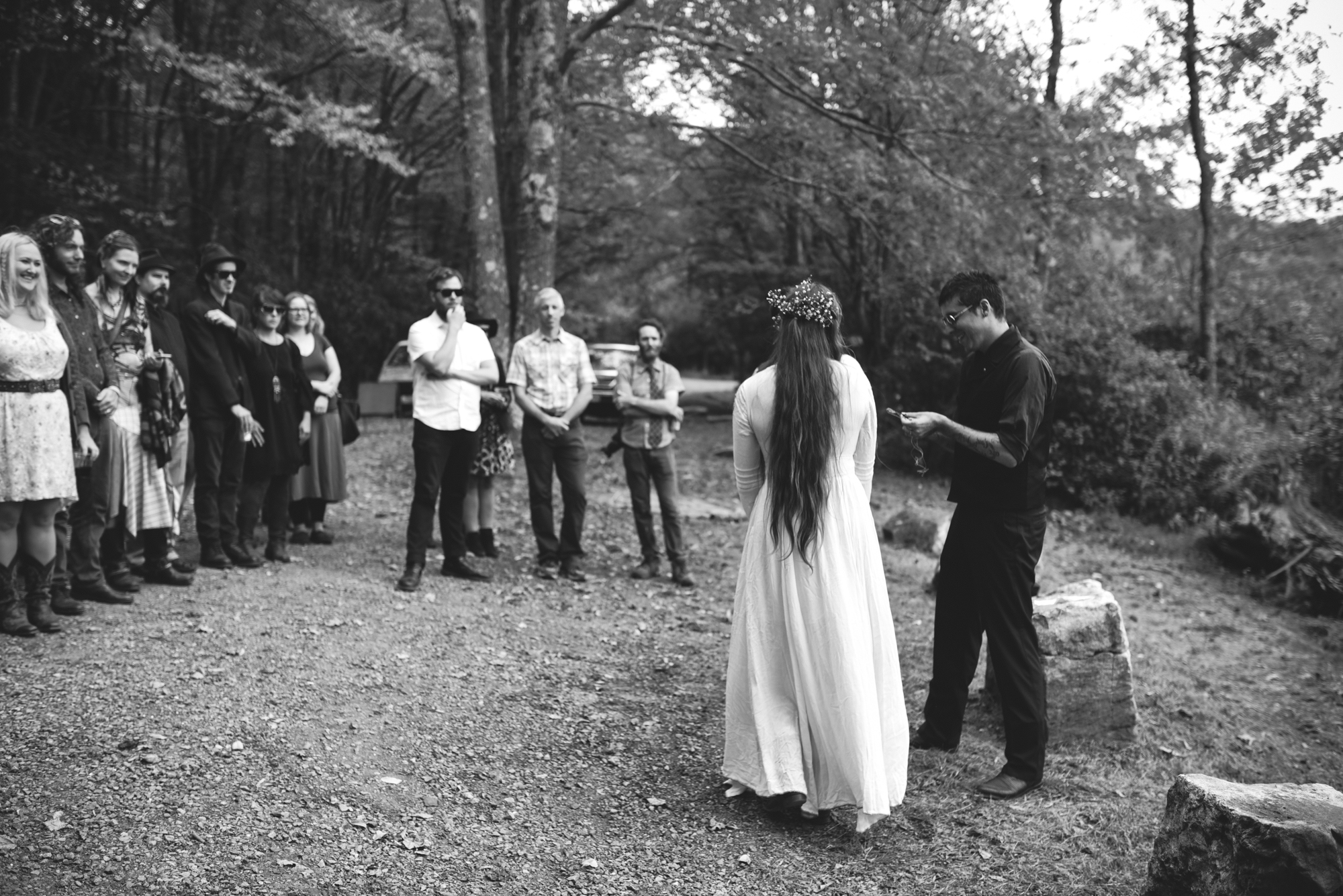 Mountain Wedding, Outdoors, Rustic, West Virginia, Maryland Wedding Photographer, DIY, Casual, guests gathered to watch ceremony, black and white ceremony, bride with long hair and flowers