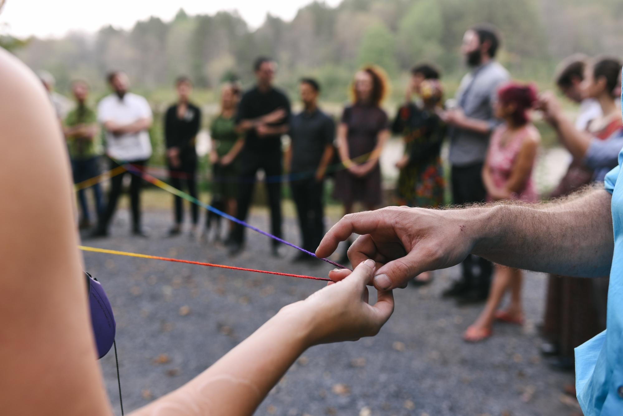Mountain Wedding, Outdoors, Rustic, West Virginia, Maryland Wedding Photographer, DIY, Casual, guests passing rainbow yarn, yarn weaving ceremony