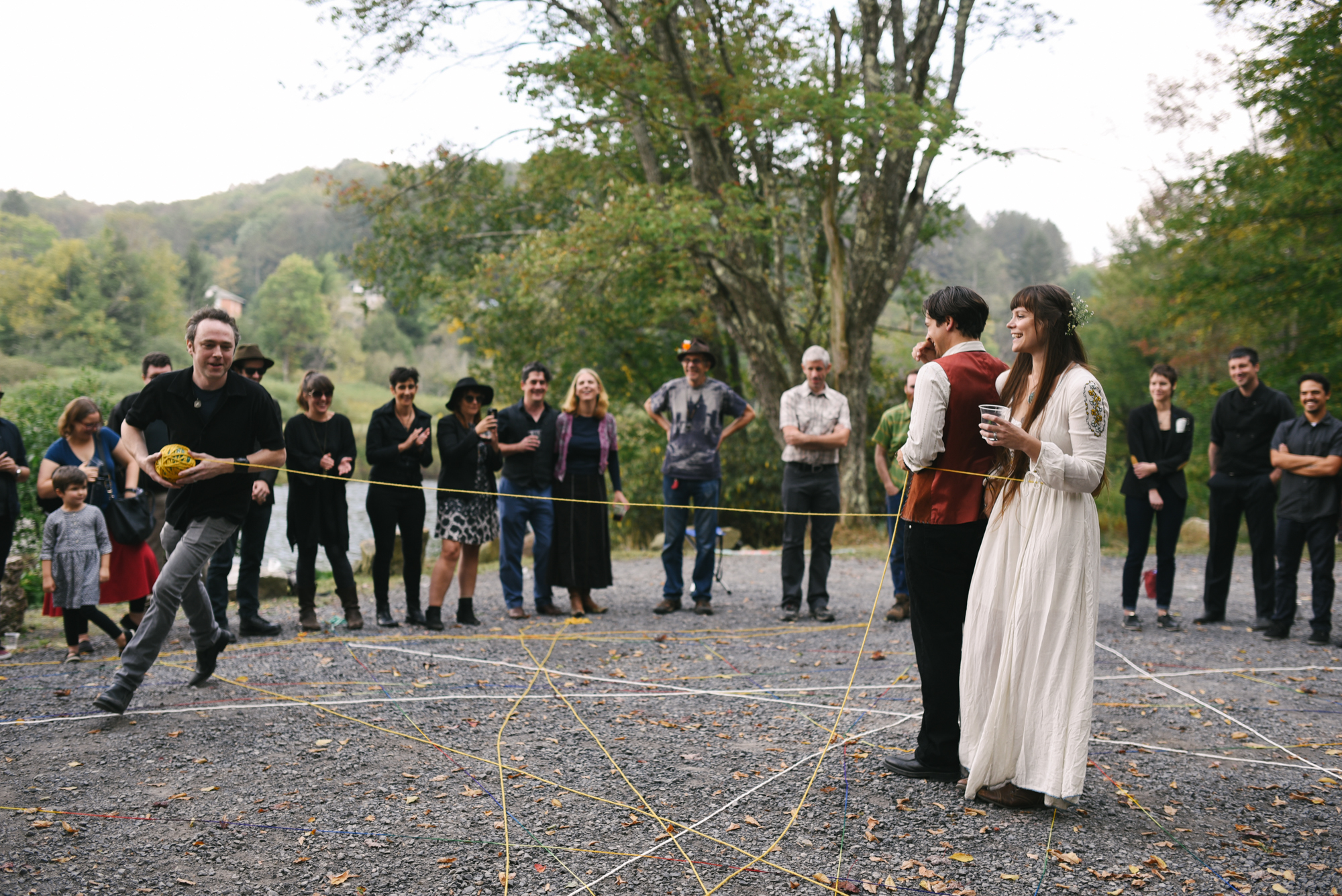 Mountain Wedding, Outdoors, Rustic, West Virginia, Maryland Wedding Photographer, DIY, Casual, bride and groom standing together being encircled with yarn, yarn weaving ceremony