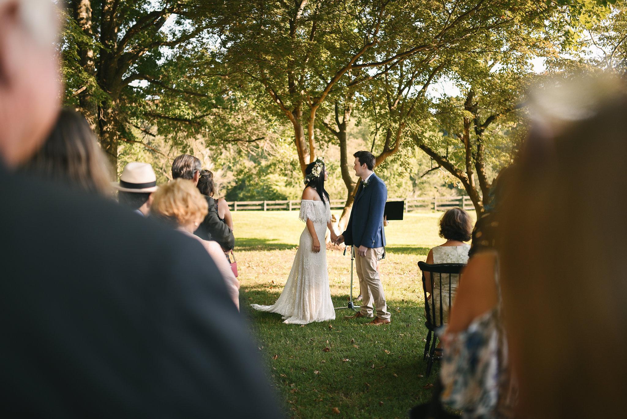Maryland, Eastern Shore, Baltimore Wedding Photographer, Romantic, Boho, Backyard Wedding, Nature, Bride and Groom Holding Hands at Ceremony, Daughters of Simone Wedding Dress