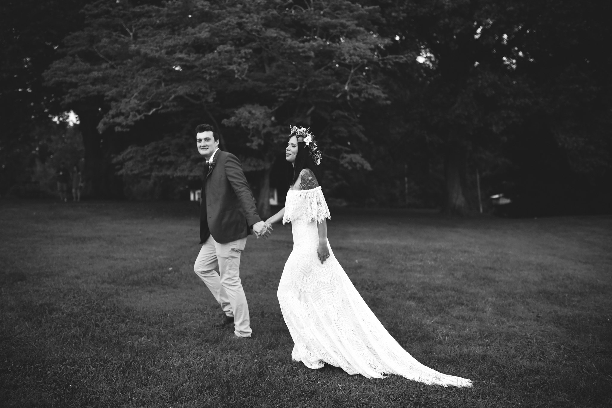 Maryland, Eastern Shore, Baltimore Wedding Photographer, Romantic, Boho, Backyard Wedding, Nature, Black and White Photo, Bride and Groom Holding Hands and Walking Through Field, Outdoor Reception, Daughters of Simone Wedding Dress