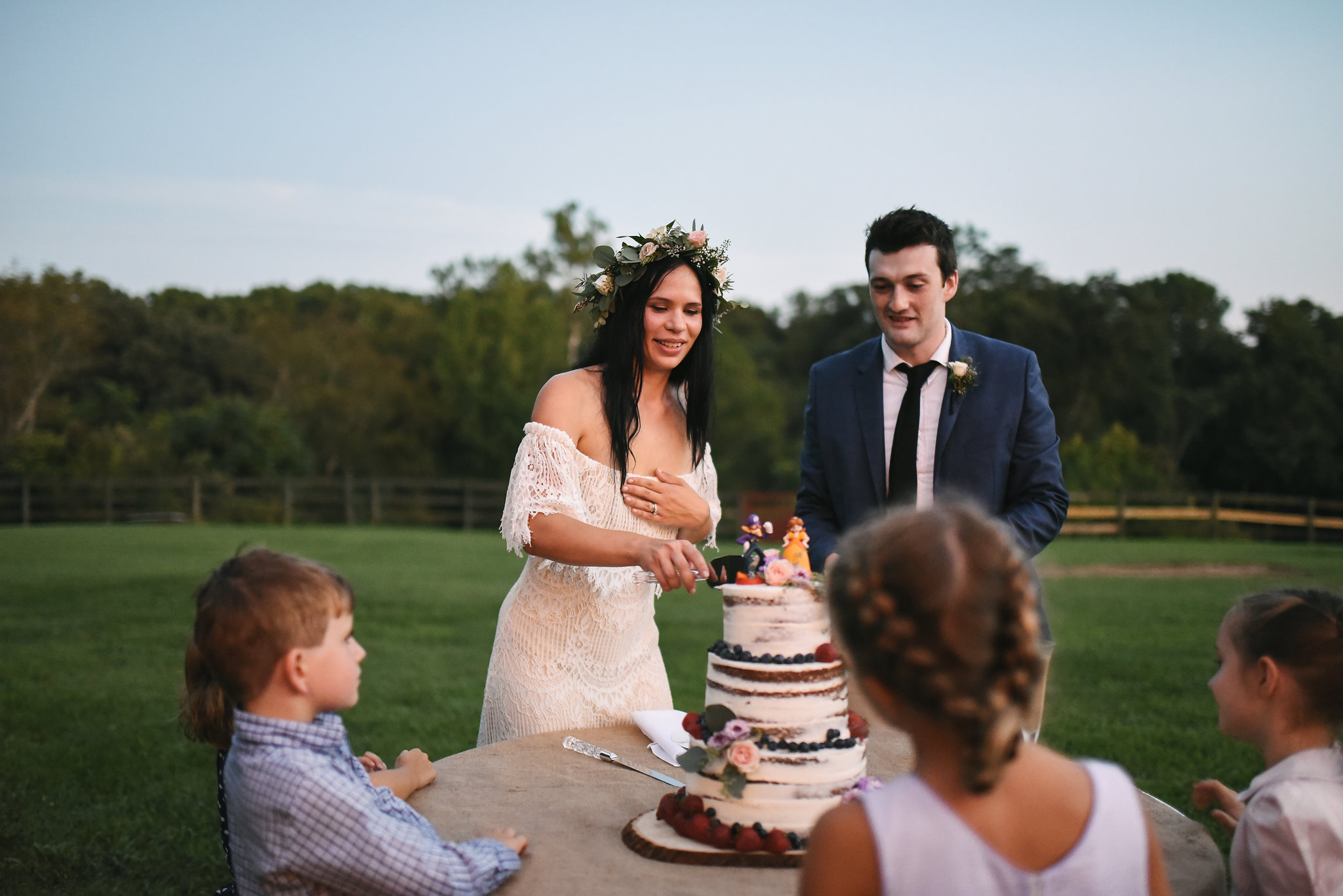 Maryland, Eastern Shore, Baltimore Wedding Photographer, Romantic, Boho, Backyard Wedding, Nature, Bride and Groom Cutting the Cake While Kids Watch, Honey Hive Bakery, Flower Crown, Outdoor Reception