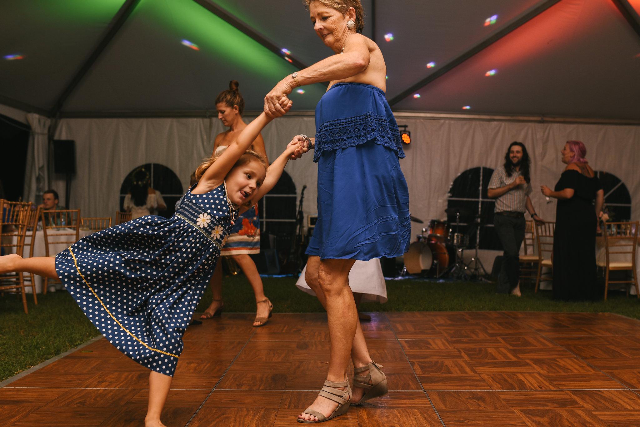 Maryland, Eastern Shore, Baltimore Wedding Photographer, Romantic, Boho, Backyard Wedding, Nature, Wedding Guest Dancing with Little Girl on Dancefloor, Little Girl Spinning