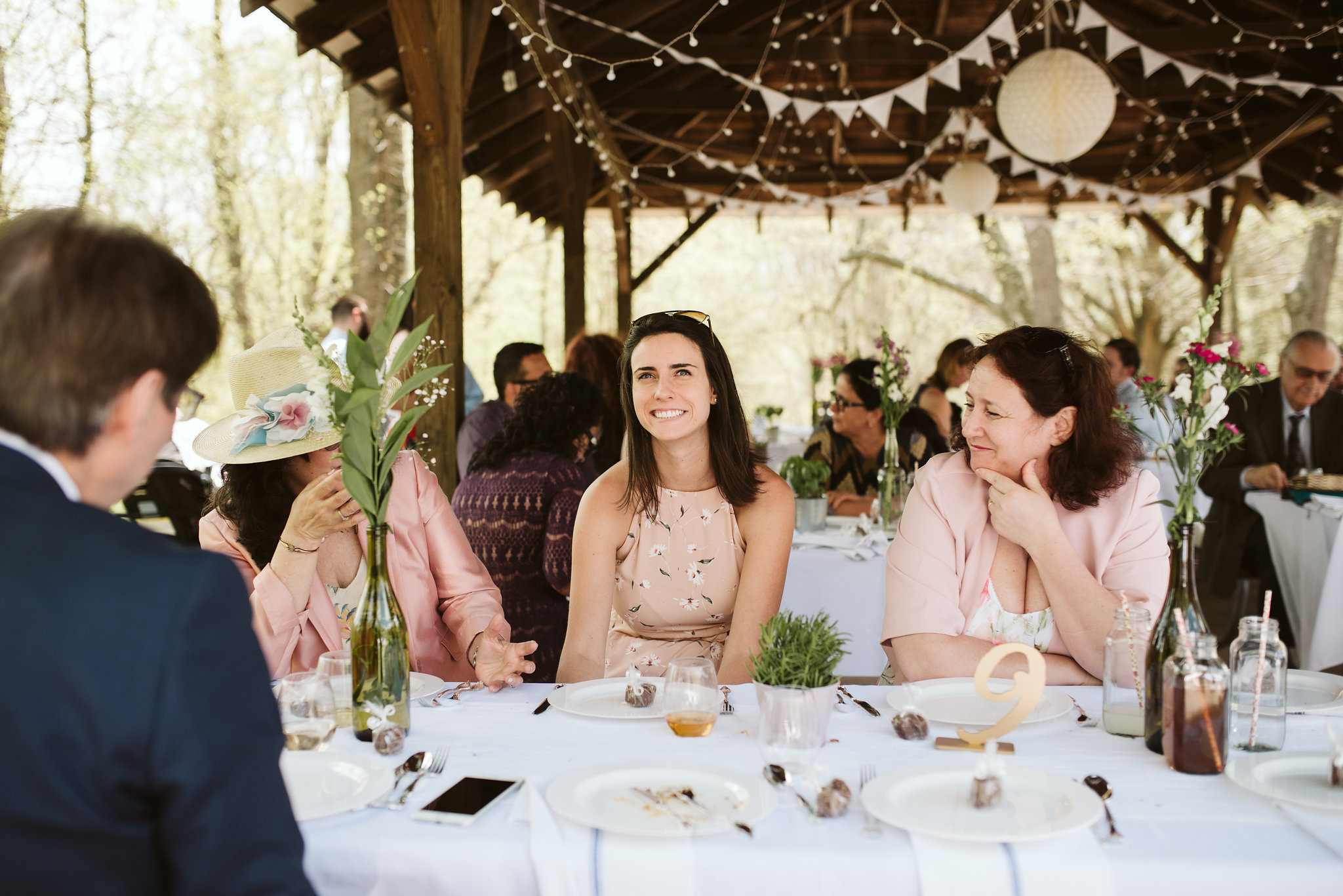 Spring Outdoor Wedding, Park, Baltimore Wedding Photographer, DIY, Classic, Upcycled, Garden Party, Romantic, Wedding Guests Laughing at Reception Tables, Wine Bottle Centerpieces