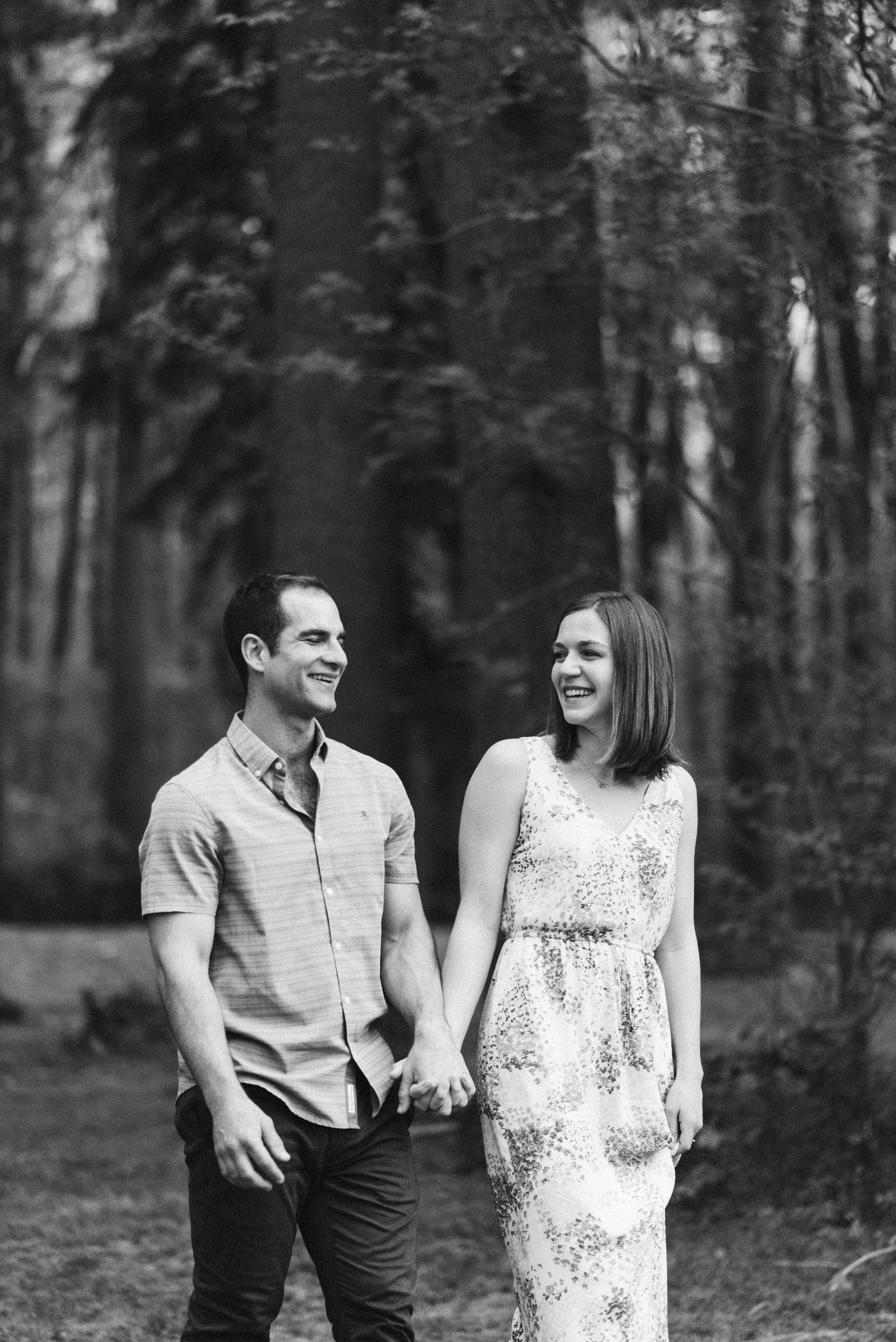 man and woman holding hands and laughing during engagement session