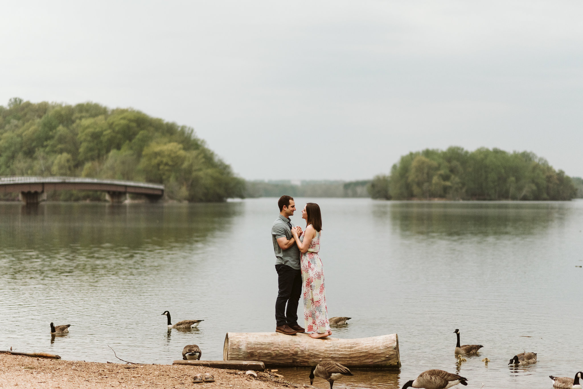 man and woman holding each other during lakefront engagement photos