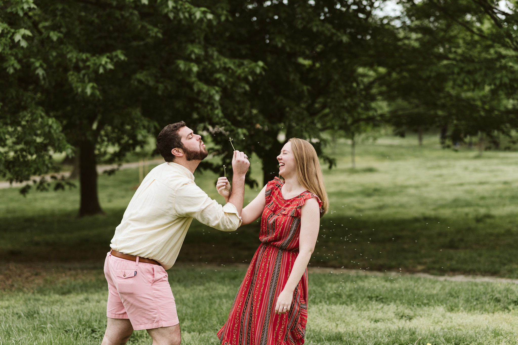 Engagement Photos, Patterson Park, Baltimore, Maryland Wedding Photographer, Casual, Fun, Nature, Silly Photo of Bride and Groom Blowing on Dandelions, Couple Laughing Together