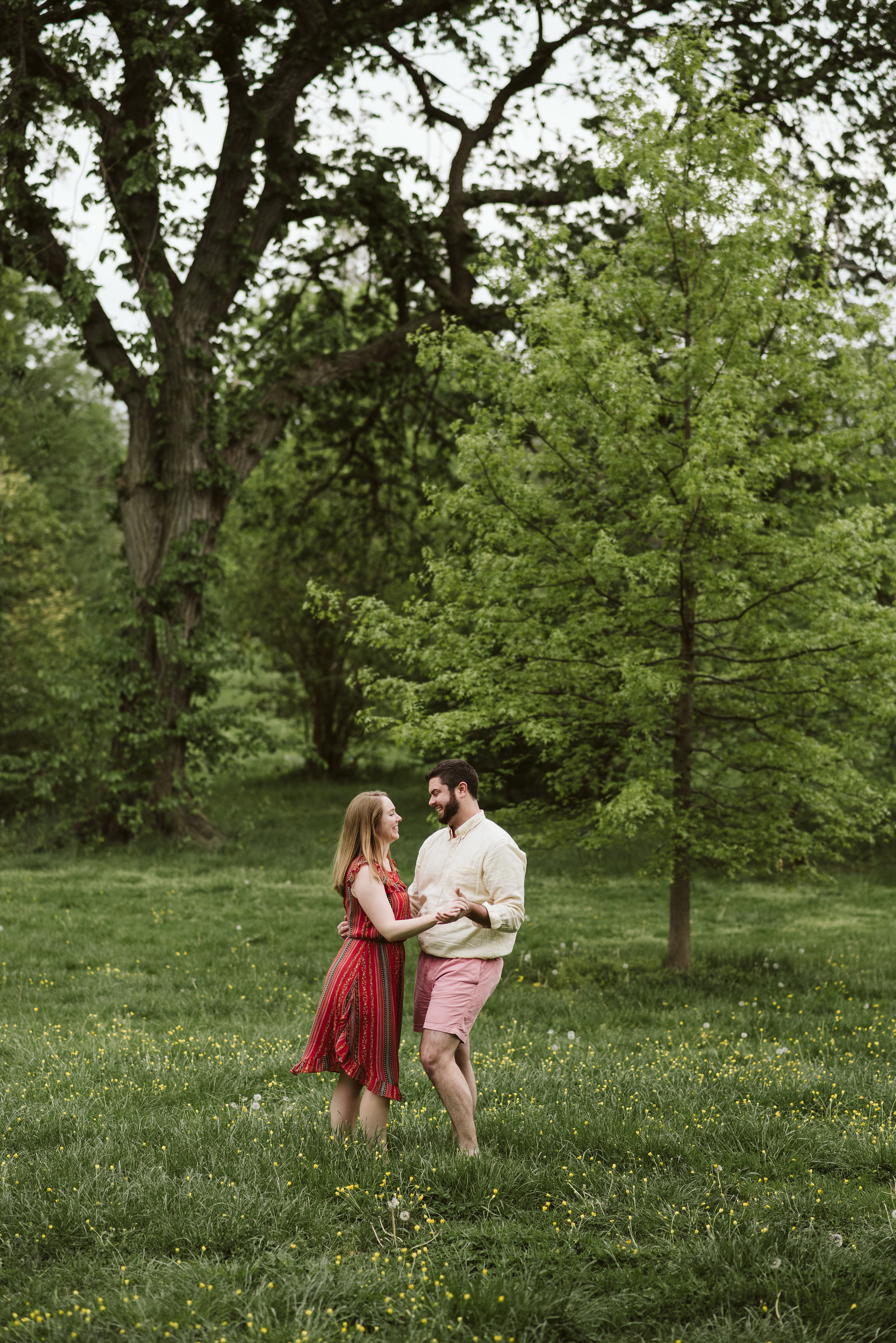 Engagement Photos, Patterson Park, Baltimore, Maryland Wedding Photographer, Casual, Fun, Nature, Bride and Groom Dancing in a Field of Buttercup Flowers