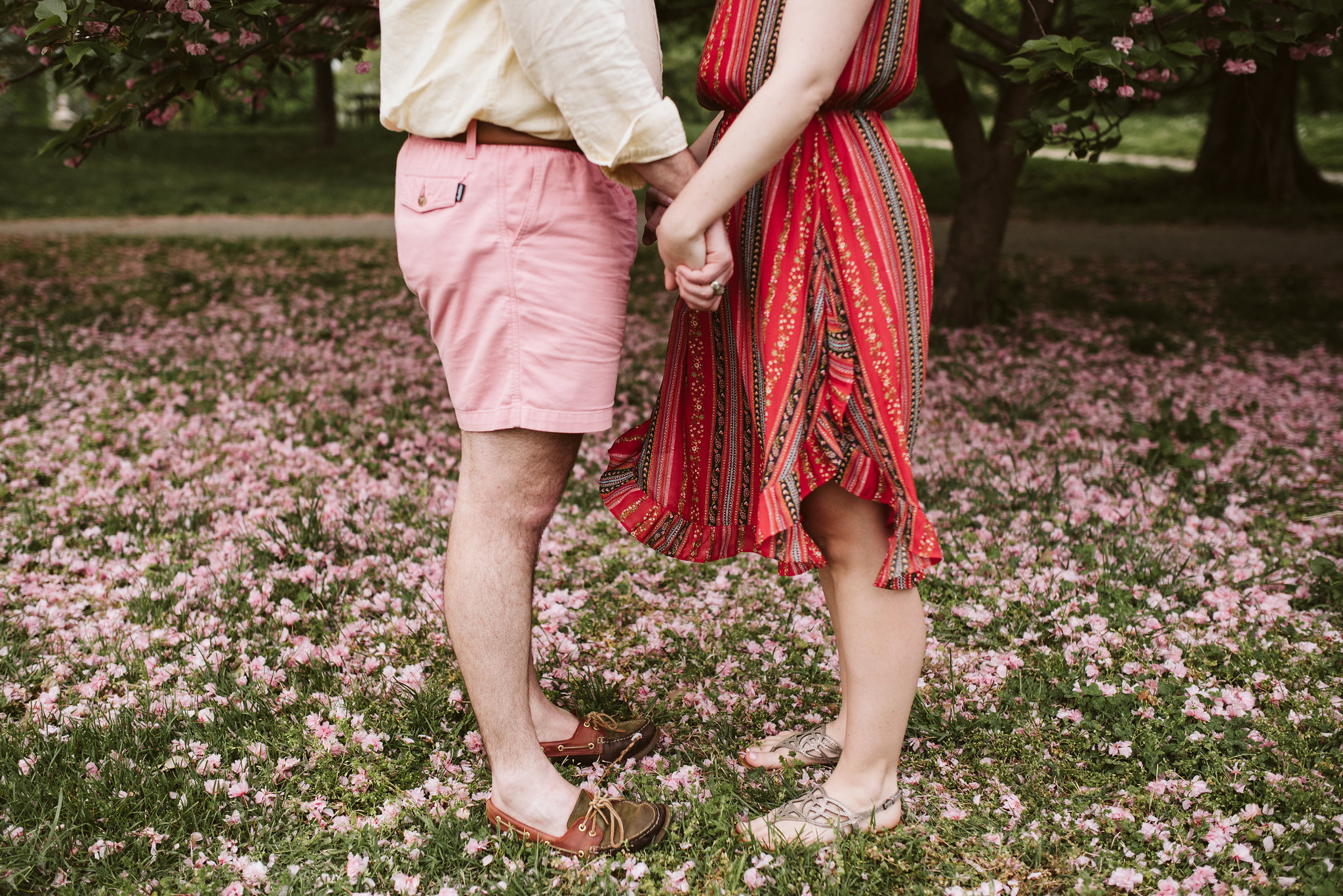 Engagement Photos, Patterson Park, Baltimore, Maryland Wedding Photographer, Casual, Fun, Nature, Sweet Photo of Bride and Groom Holding Hands Surrounded by Pink Flowers, Spring