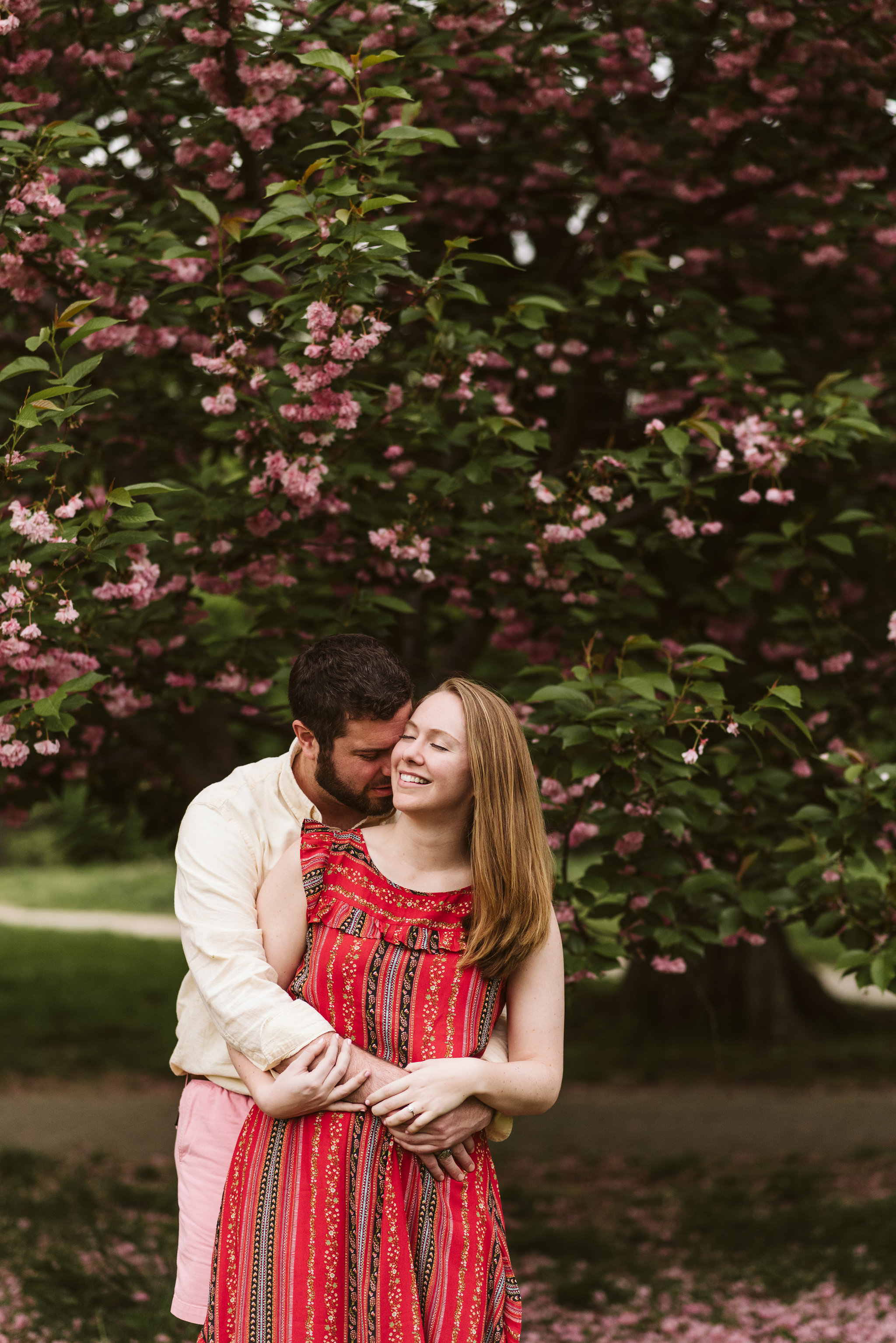 Engagement Photos, Patterson Park, Baltimore, Maryland Wedding Photographer, Casual, Fun, Nature, Couple Holding Each Other with Their Eyes Closed, Bride and groom Hugging, Springtime