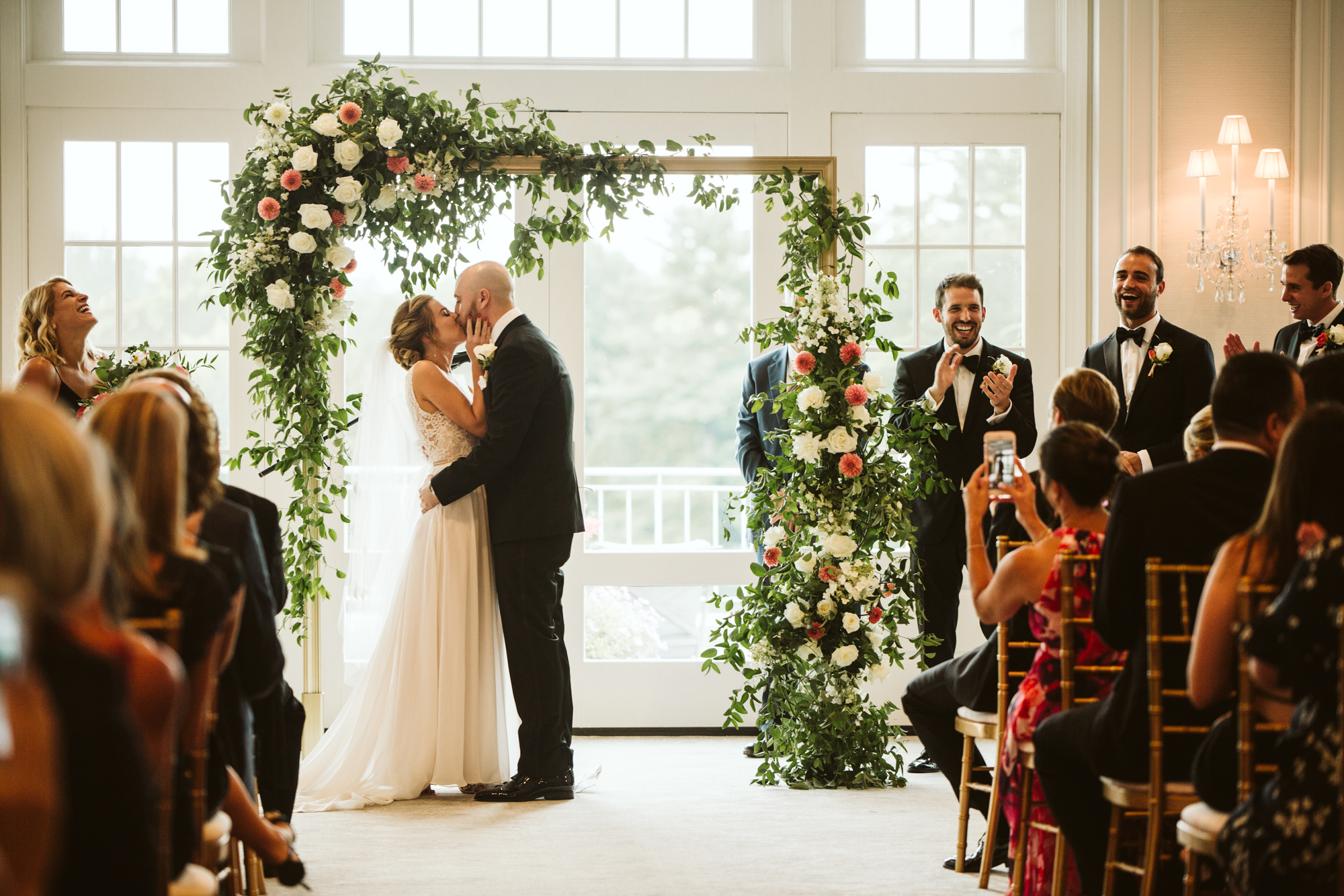 Elegant, Columbia Country Club, Chevy Chase Maryland, Baltimore Wedding Photographer, Classic, Traditional, Jewish Wedding, Bride and Groom Under Floral Archway, Meg Owen Floral Designs, First Kiss