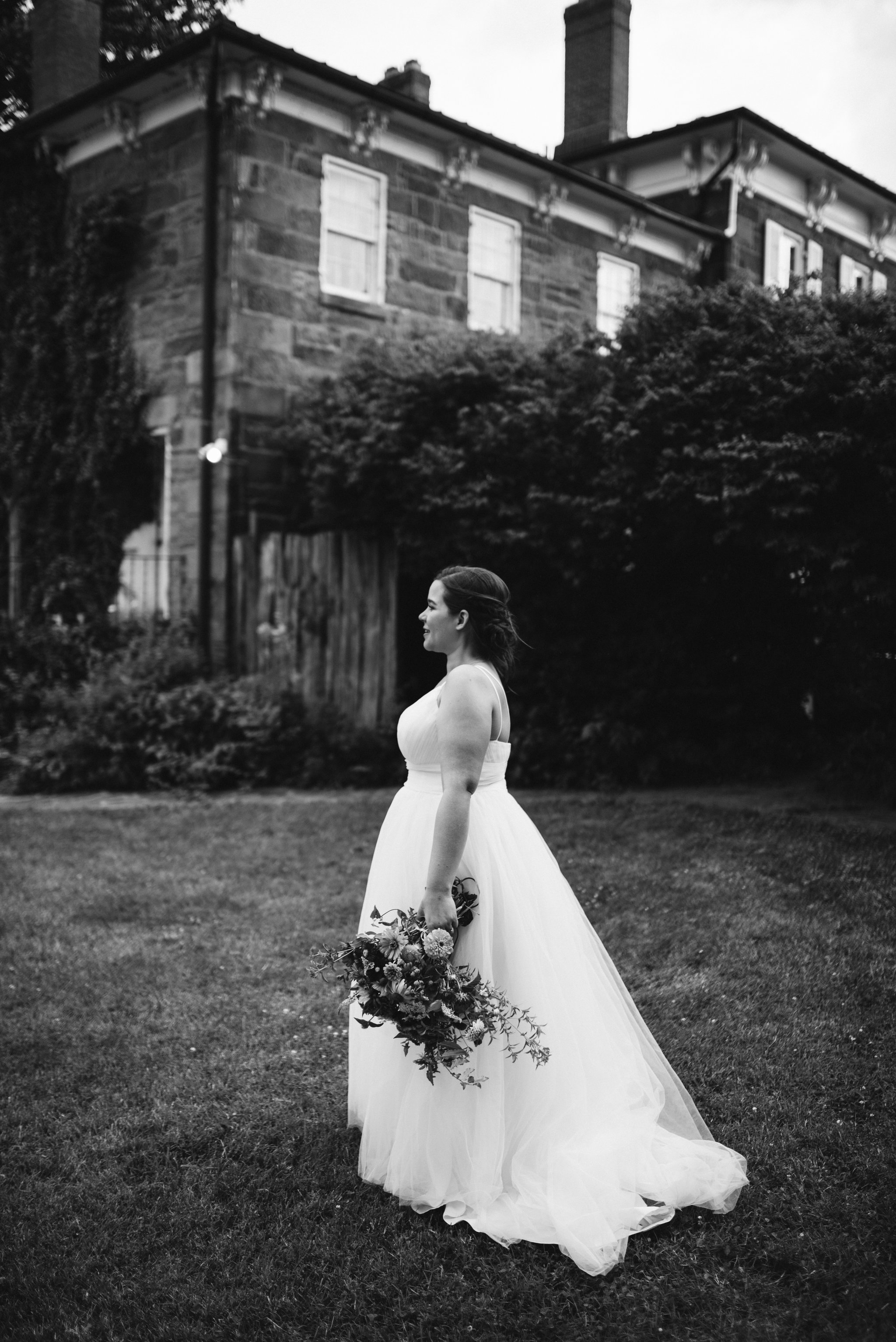 Rocklands Farm, Maryland, Intimate Wedding, Baltimore Wedding Photographer, Sungold Flower Co, Rustic, Romantic, Barn Wedding, Bride Walking Across Lawn Holding Flowers, Black and White Photo