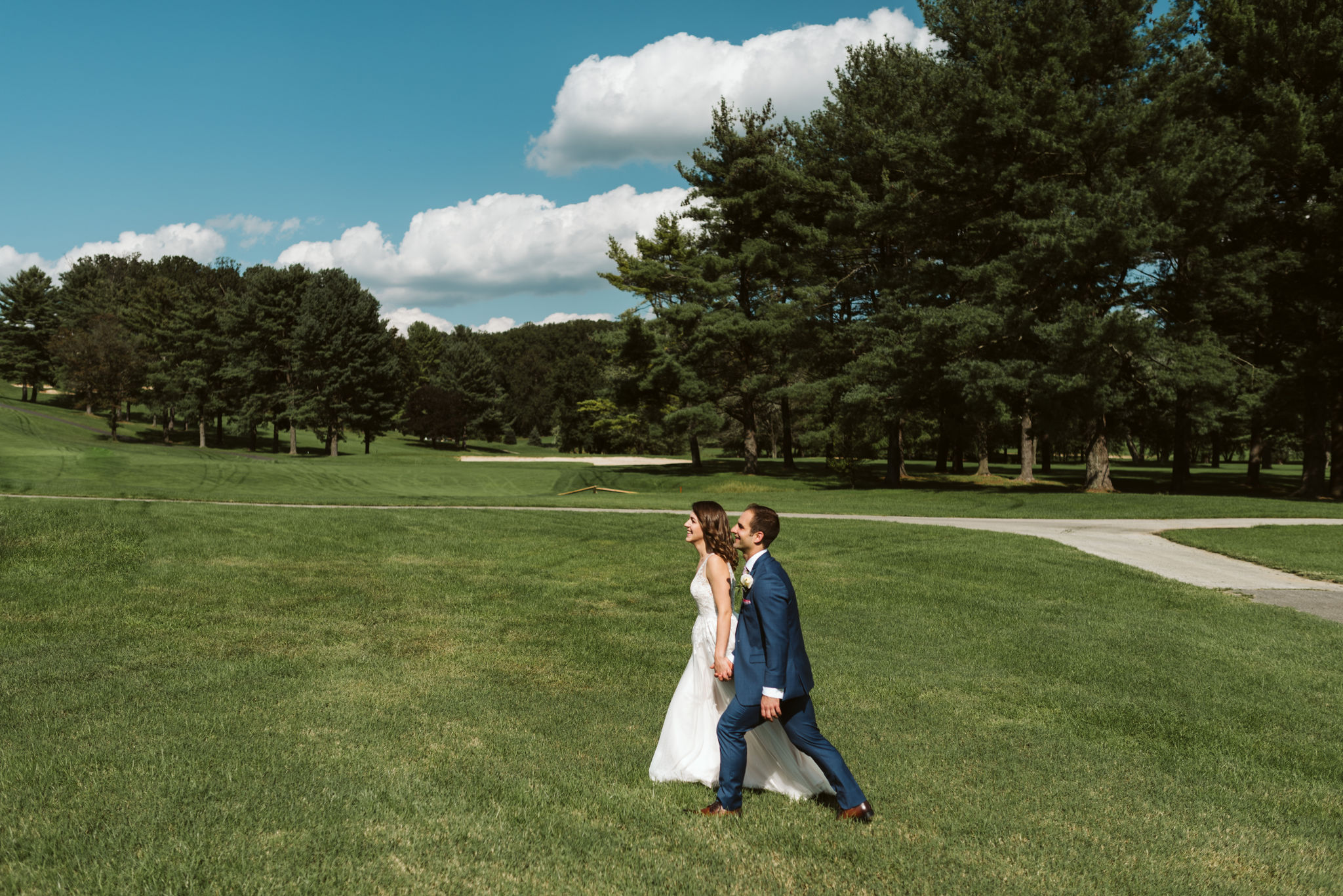 Phoenix Maryland, Baltimore Wedding Photographer, Eagle's Nest Country Club, Classic, Romantic, Spring, Bride and Groom Walking through the Grass Hand in Hand, Blue Suit from Generation Tux