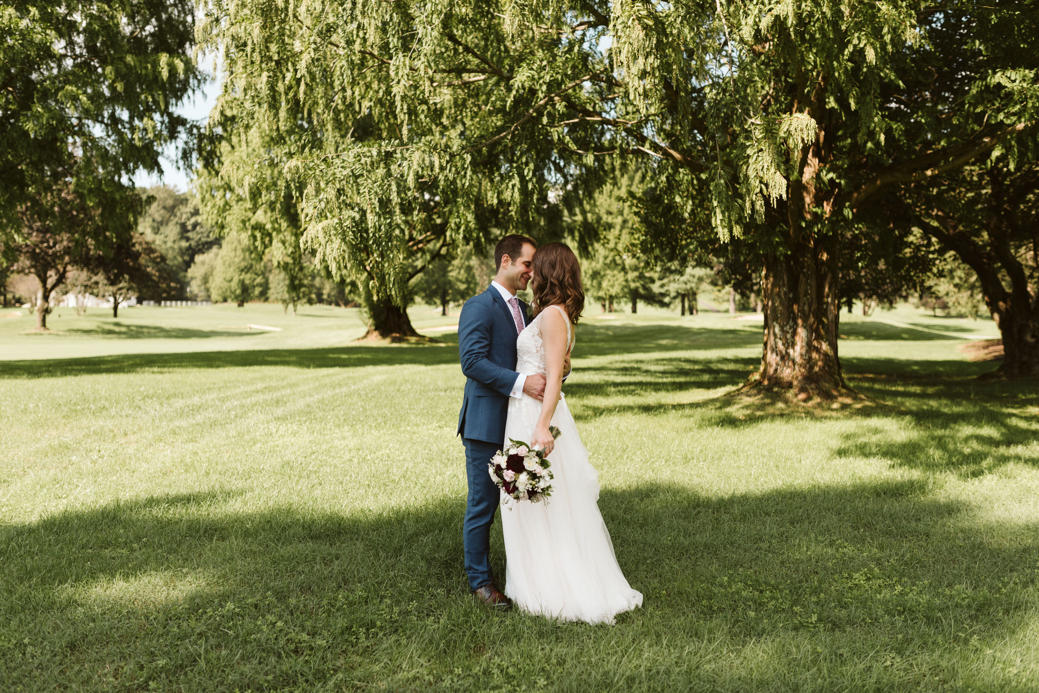 Phoenix Maryland, Baltimore Wedding Photographer, Eagle's Nest Country Club, Classic, Romantic, Spring, Bride and Groom Kissing Under the Trees, Dundalk Florist, BHLDN Dress, Blue Generation Tux Suit