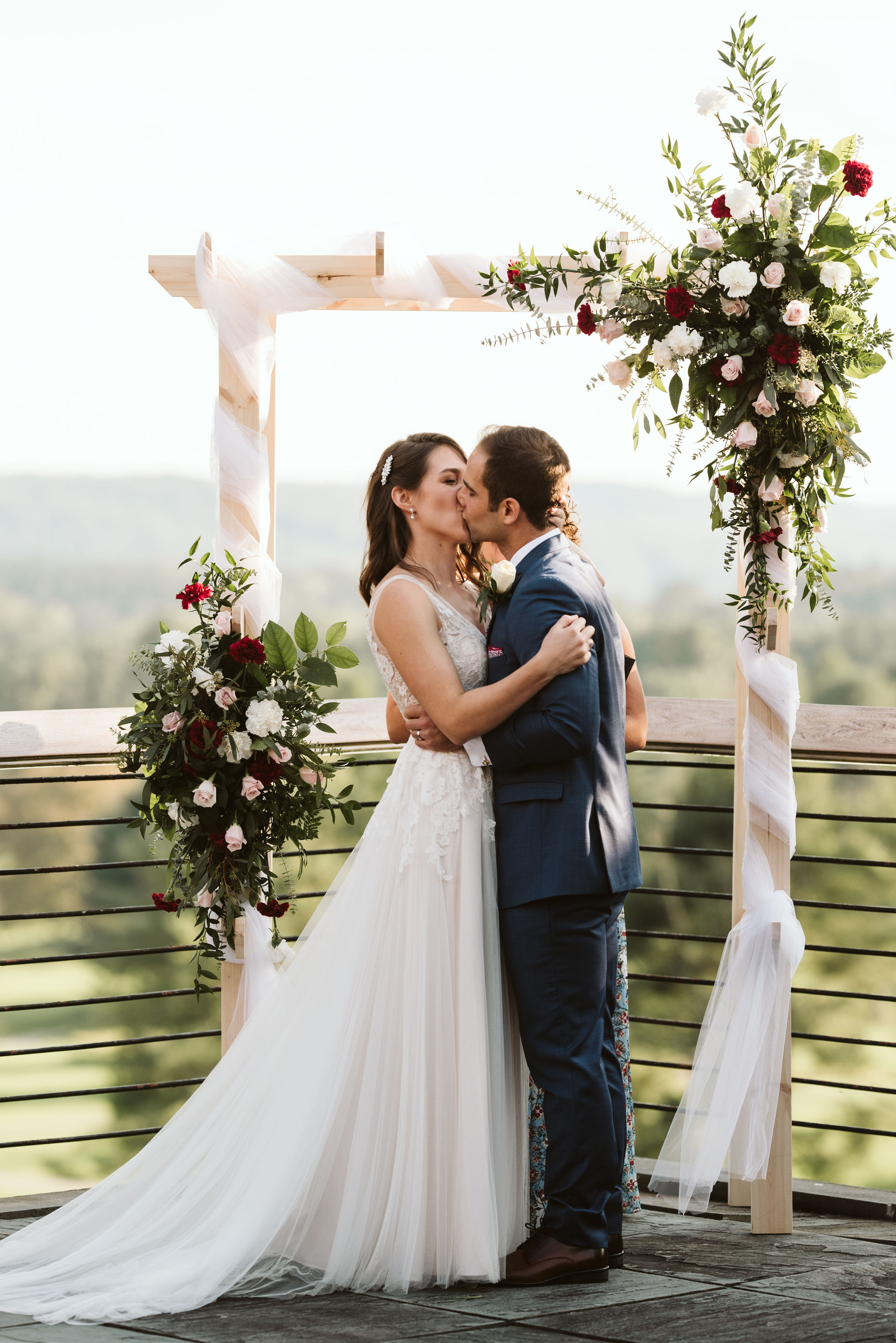 Phoenix Maryland, Baltimore Wedding Photographer, Eagle's Nest Country Club, Classic, Romantic, Spring, Bride and Groom Share First Kiss, Just Married, Red and White Floral Arrangements, Dundalk Florist, BHLDN Dress