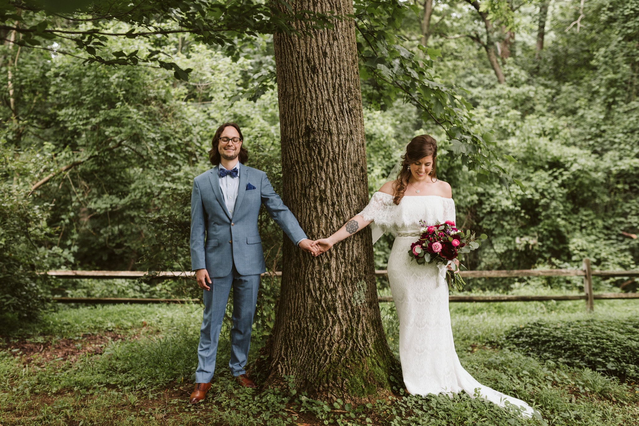 first look inspiration bride and groom holding hands around tree