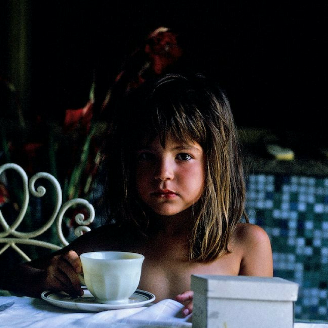 """This is me as a child in Argentina at my grandmother's table in her """"magical"""" backyard drinking mate."""