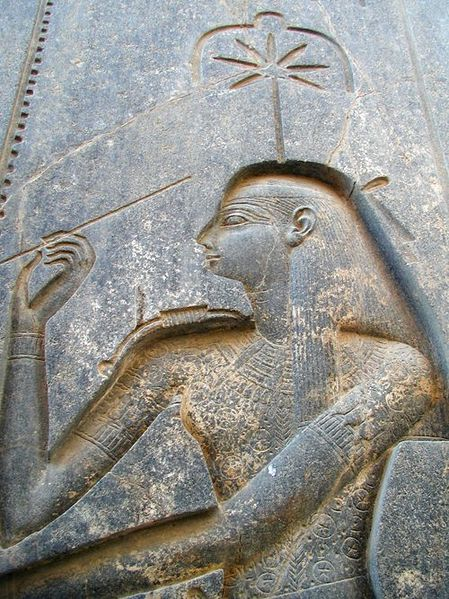 The scribe goddess Seshat, who like her consort Thoth, embodies wisdom, knowledge, and all the disciplines of priestly learning. Depicted on the seated statue of Ramese II, Temple of Amum, Luxor, circa 1250 BCE.