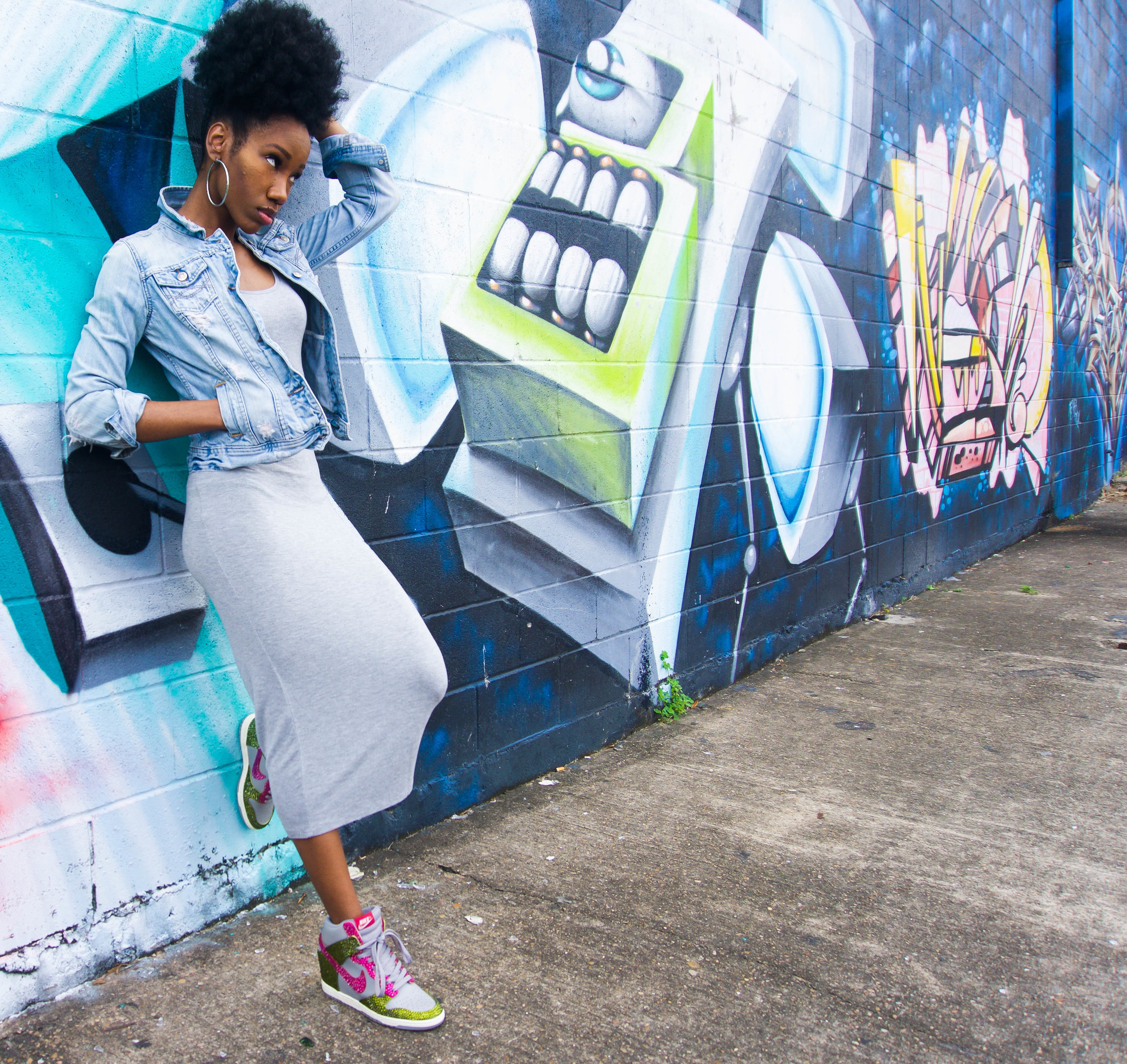 Dresses to wear with sneakers? Yes, it's possible! Got my shoes bedazzled and a basic dress to complete this sneaker outfit. You'll also find a couple of dresses in this post to help you develop your own sneaker style. Photo taken in Houston, in front of a graffiti mural. Rocking some custom made nikes (shoes bedazzled), denim jean jacket, hoop earrings, and a gray bodycon dress from Forever 21. A sneaker outfit for women.