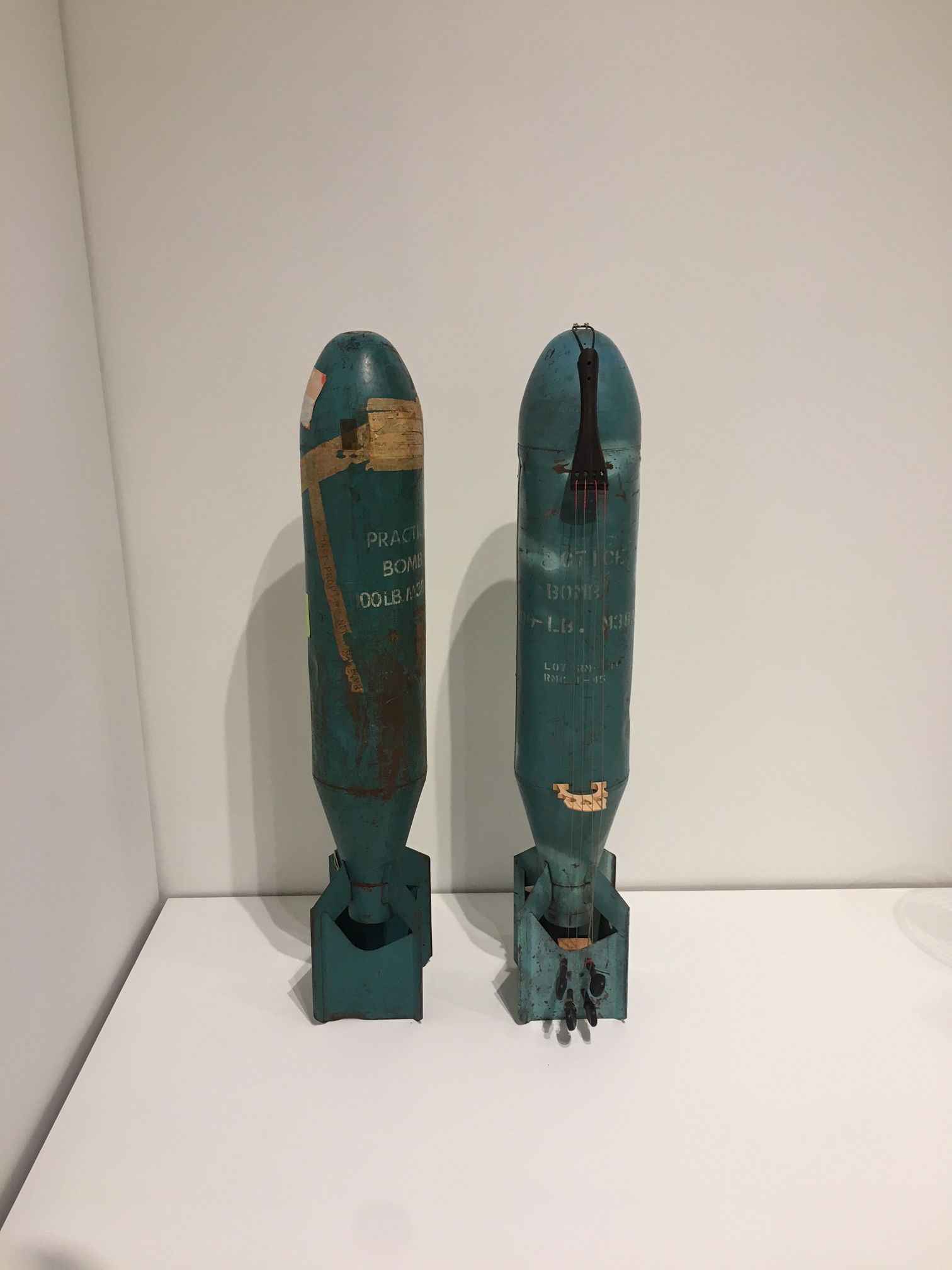 Bomb Cello, Charlotte Moorman, 1965 (left) Bomb Cello, c. 1990 (right). Paint and mixed media on metal, 48 x 10 x 10 in. each. Courtesy Sammlung Hoffmann, Berlin.