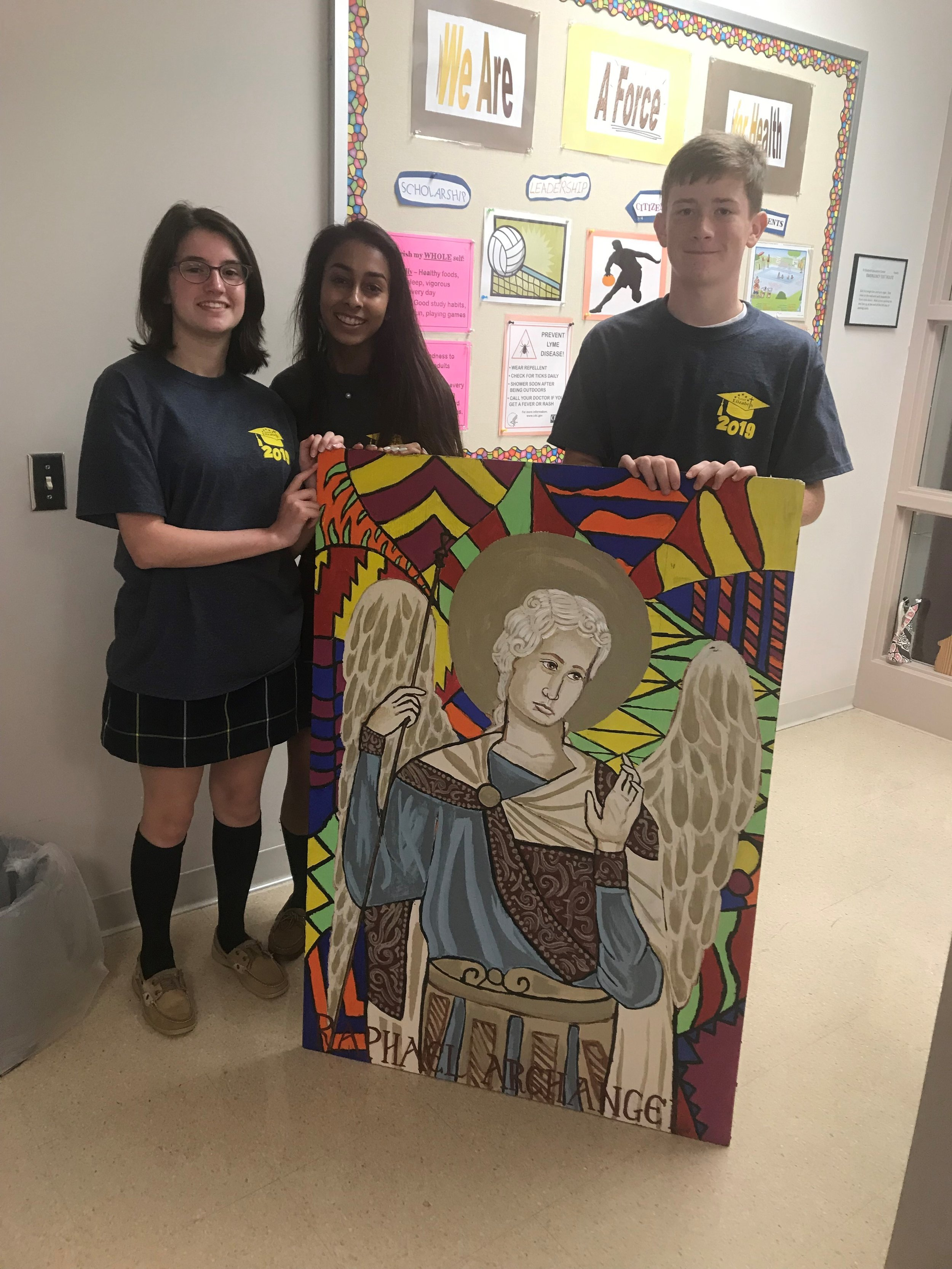 June 11, 2019: (From R): Students Stella R., Mikhela P. and Ryan G., along with art teacher Mrs. Liz Griffin, presented the Class of 2019 art gift to the school. This painting on plywood is of Saint Raphael, Archangel, and patron saint of the sick. It will be hung in the Nurse's office over the summer. Thank you to the Class of 2019 for this beautiful gift! (Photo: Mrs. Sara Richardson, Communications Coordinator)