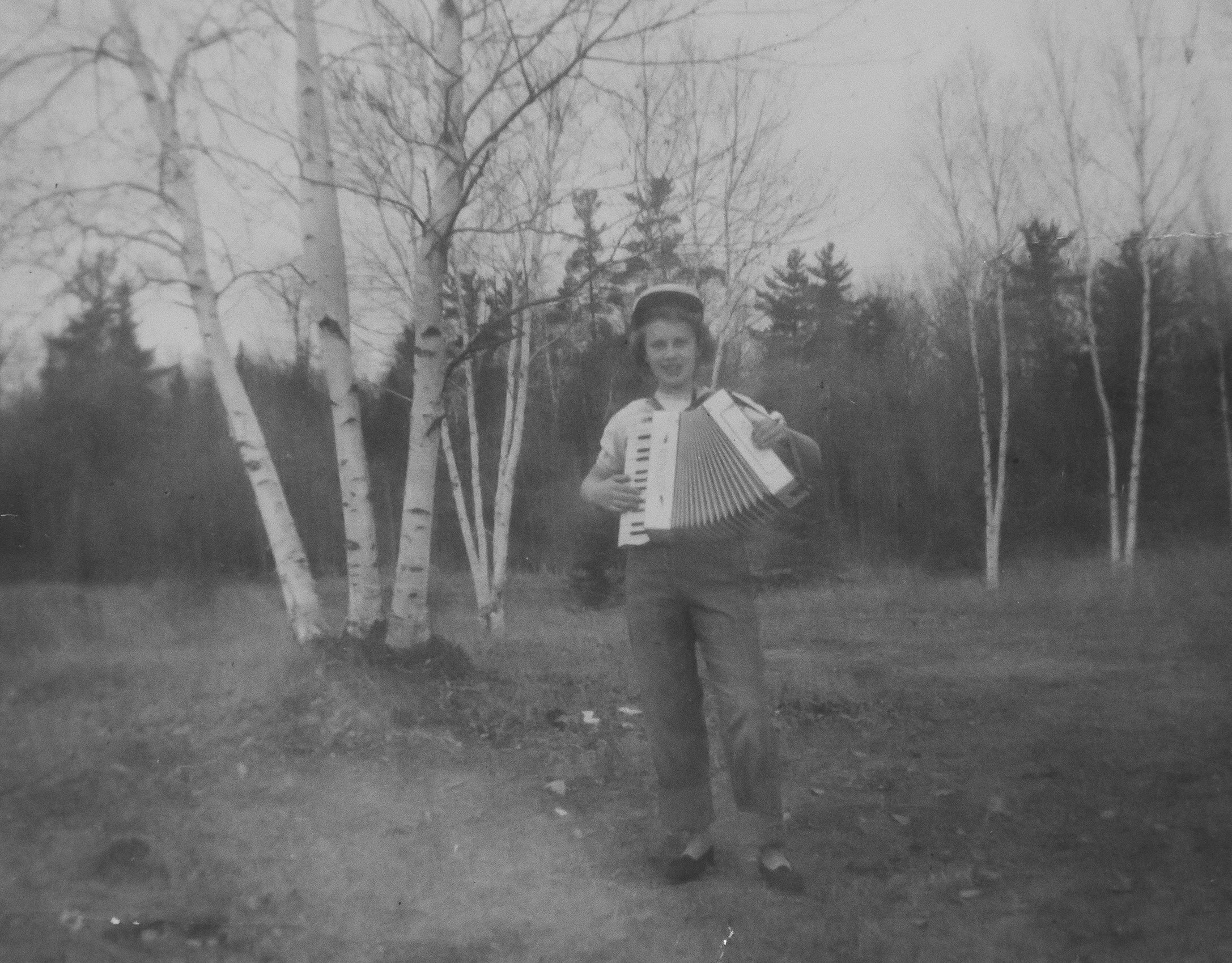 "Caption written by my dad. ""My mother as a teenager playing the accordion at the old Bodin homestead west of Glen, Minnesota (1949 approx). Her father played in the marching band in WW I, and he taught her how to play the accordion before his untimely death (my mother was only 11). Mom has always loved music, and I remember her playing the accordion and organ many times in my youth. She was so proud of us kids (and grandkids) when we also learned how to play instruments. She was fun, creative and adventuresome, traits I see today in my children and grandchildren."""