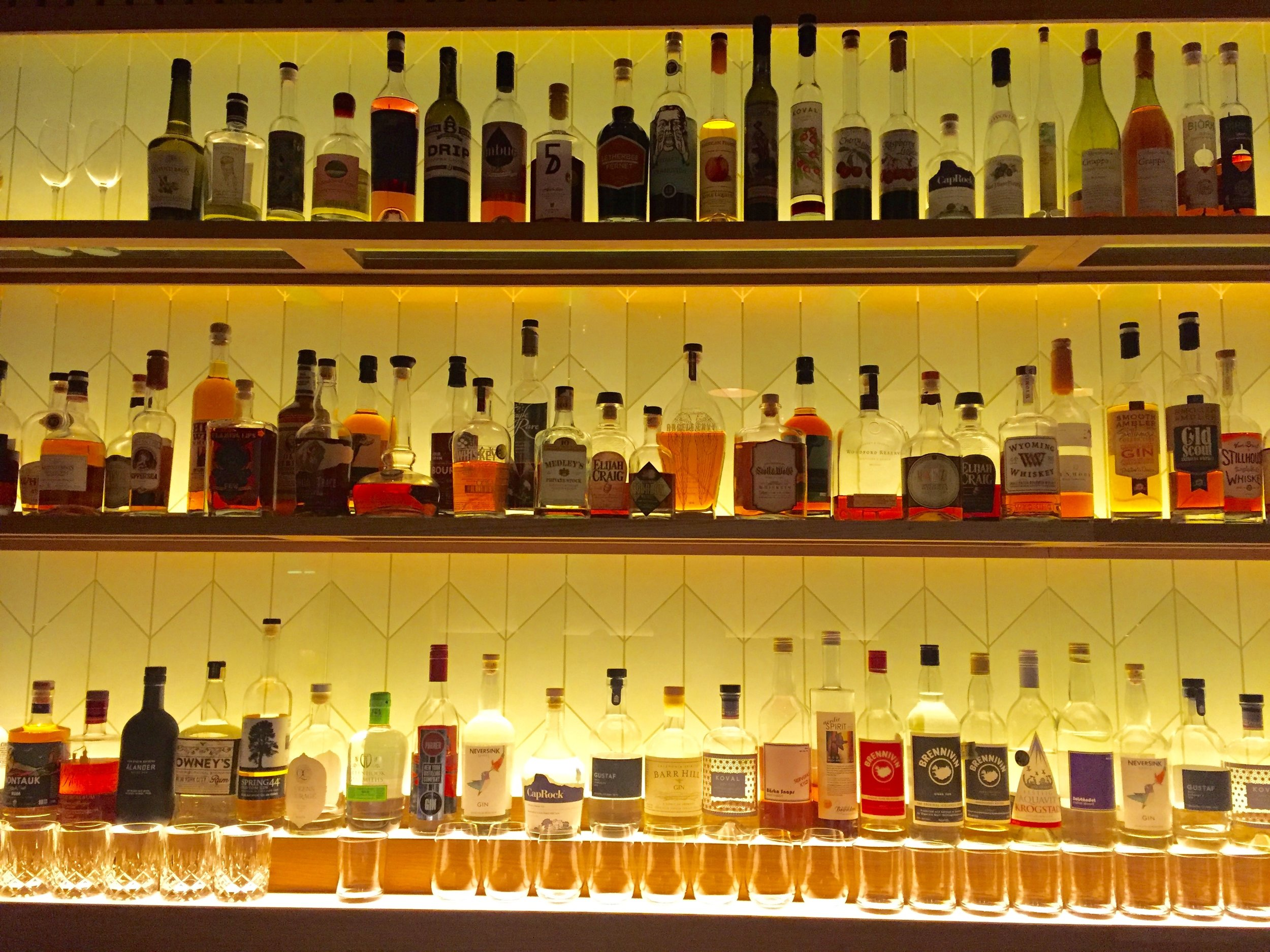 The backlit bar shelves at Argern hold a variety of artisan bottles with amber and gold liquids