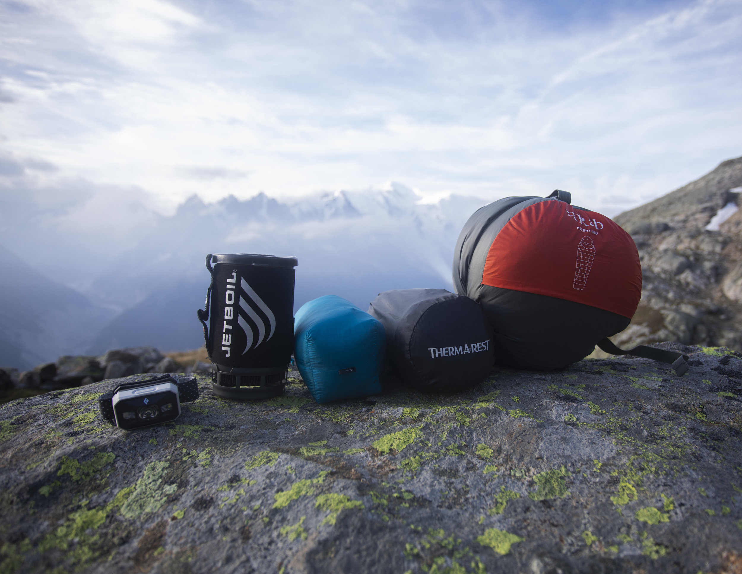 Some of my basic gear with the Mont Blanc behind.  From left to right. Black Diamond Storm headlamp, Jetboil, Arc'teryx Cerium LT Down jacket, Thermarest NeoAir Xtherm, Rab Ascent 900 sleeping bag.