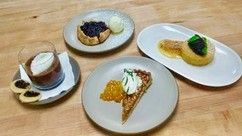 Italian desserts starting from the top: Blueberry crostada with olive oil gelato, olive oil polenta cake with fig compate, pine nut tart with creme fraiche and candied orange peel, and chocolate budino with salted caramel, whipped cream and shortbread cookies with cherry compote