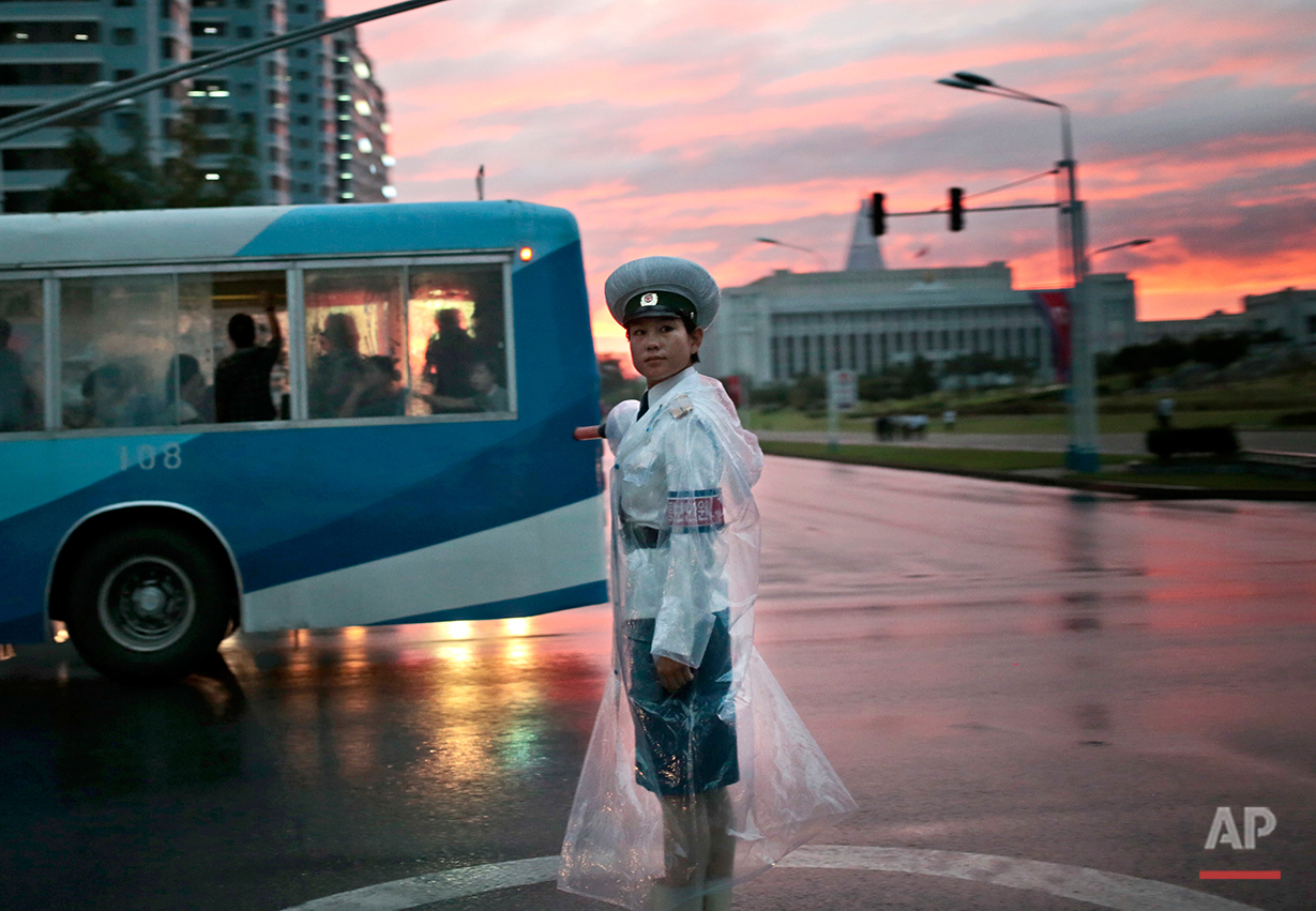 A traffic police officer directs vehicles at a street junction during sunset in Pyongyang, North Korea, Thursday, Aug. 25, 2016. (AP Photo/Dita Alangkara)