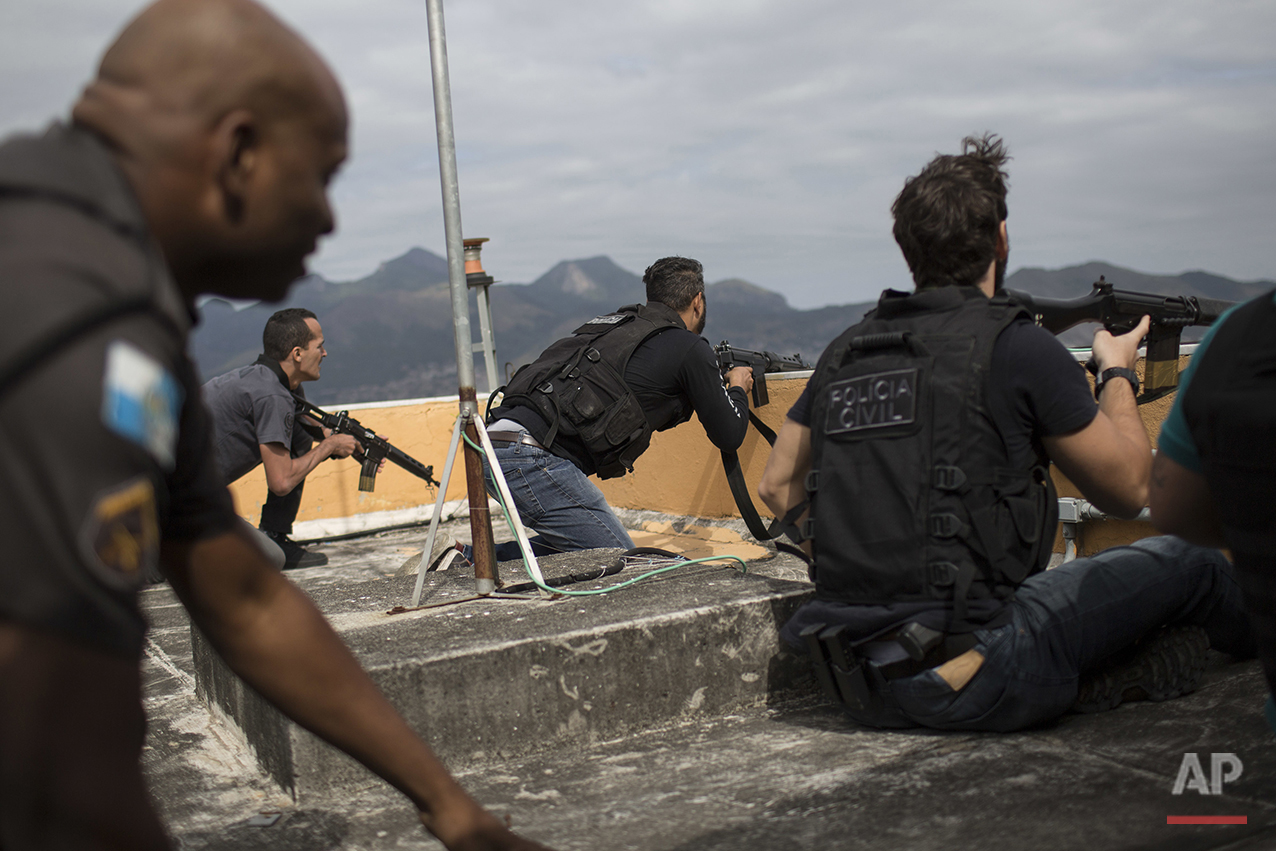 "In this July 7, 2016 photo, police exchange gunfire with drug traffickers at the ""pacified"" Alemao slum complex in Rio de Janeiro, Brazil. Half a dozen officers had entrenched themselves behind a cable car station while they shot it out with suspected drug traffickers in the sprawling cluster of slums in north Rio. Shootouts erupt daily, even in slums where community policing programs had successfully rewritten the narrative in recent years. (AP Photo/Felipe Dana)"