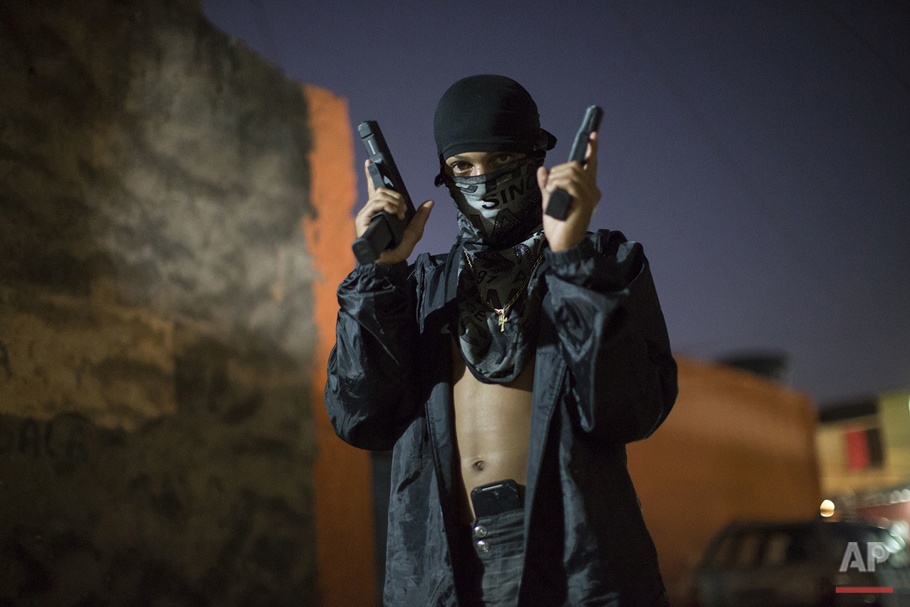 In this July 11, 2016 photo, a young, masked drug trafficker poses for photos holding his guns at a slum in Rio de Janeiro, Brazil. Teenagers openly tote guns while they work as guards, lookouts and distributors for drug lords operating just a few miles (kilometers) from where hundreds of thousands and tourists and athletes will be for the Aug. 5-21 Olympic Games. (AP Photo/Felipe Dana)