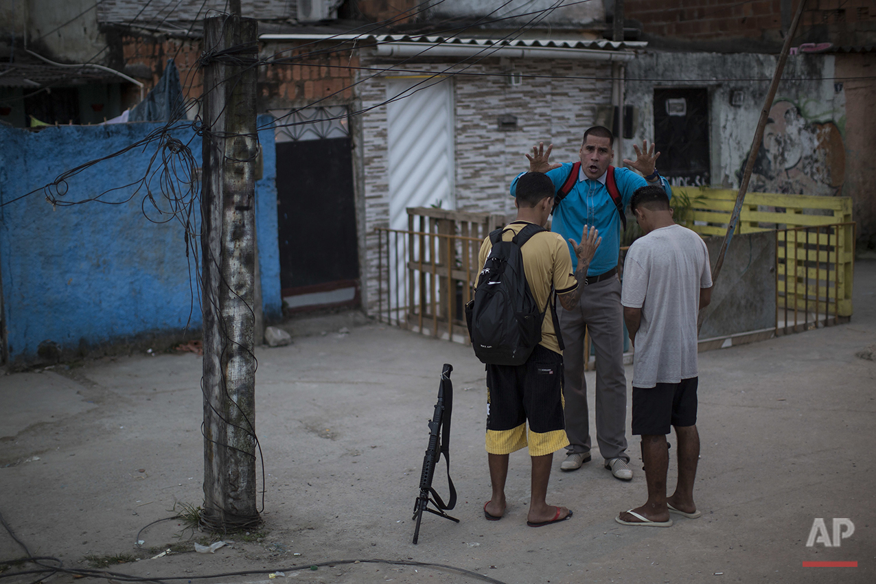 In this July 16, 2016 photo, pastor Nilton blesses two young drug traffickers at a slum in Rio de Janeiro, Brazil. Many of the young drug traffickers have an immense respect for the pastor, a former drug trafficker. It's not uncommon to see young men set their weapons down, but only long enough to receive his blessing. (AP Photo/Felipe Dana)