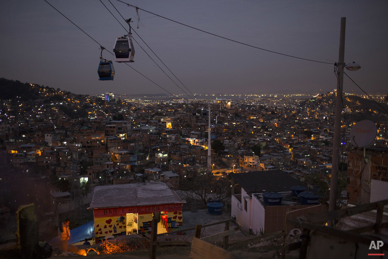 In this July 19, 2016 photo, cable cars transport commuters over the Complexo do Alemao, a sprawling cluster of slums in north Rio de Janeiro, Brazil. Just a short drive from upscale Rio districts like Ipanema and Copacabana, steep and narrow entryways lead to slums where poverty and gun violence dominate daily life for hundreds of thousands of residents.(AP Photo/Felipe Dana)