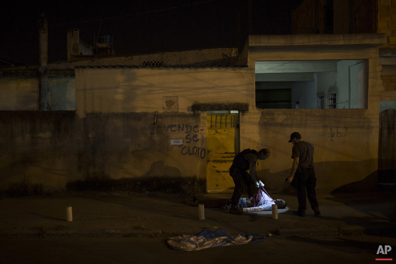In this July 16, 2016 photo, police responding to a call find the body of a young black man in the middle of a residential street in Caxias, greater Rio de Janeiro, Brazil.  (AP Photo/Felipe Dana)