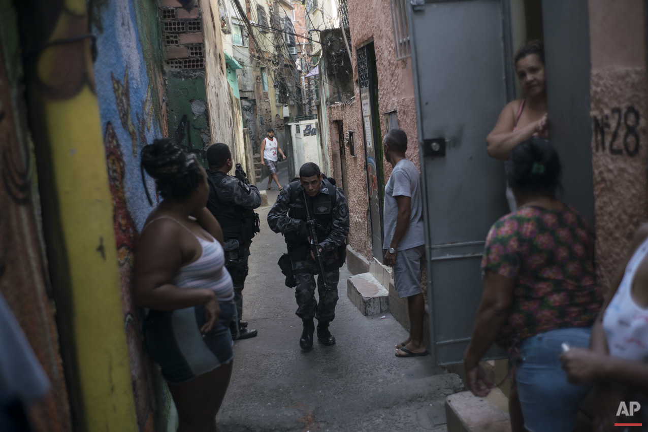 "In this June 29, 2016 photo, a police officer patrols among residents during an operation against drug traffickers at the ""pacified"" Jacarezinho slum in Rio de Janeiro, Brazil. The Pacification Police Units, known by the Portuguese acronym UPP, were created in 2008, setting up community stations in at-risk areas, mostly near sports venues, posh tourist districts and downtown. A drug gang leader called the program a ""facade."" He said that drug dealers were initially worried and kept a low profile, but soon it was back to business as usual. (AP Photo/Felipe Dana)"