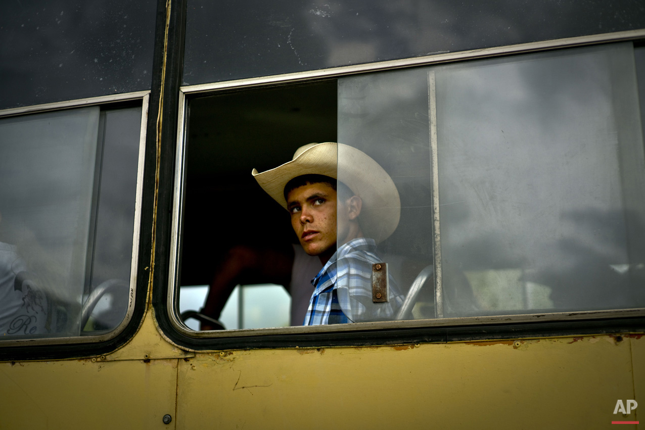 In this July 29, 2016 photo, a young cowboy looks out from a bus window as he waits to be transported via bus to an improvised rodeo event at a farm in Sancti Spiritus, central Cuba. In Sancti Spiritus' cattle country, 80 children are enrolled in the non-governmental organization called Future Ranchers association, which struggles to find the funds for basic needs like gasoline for the vehicles taking the students to competitions. (AP Photo/Ramon Espinosa)