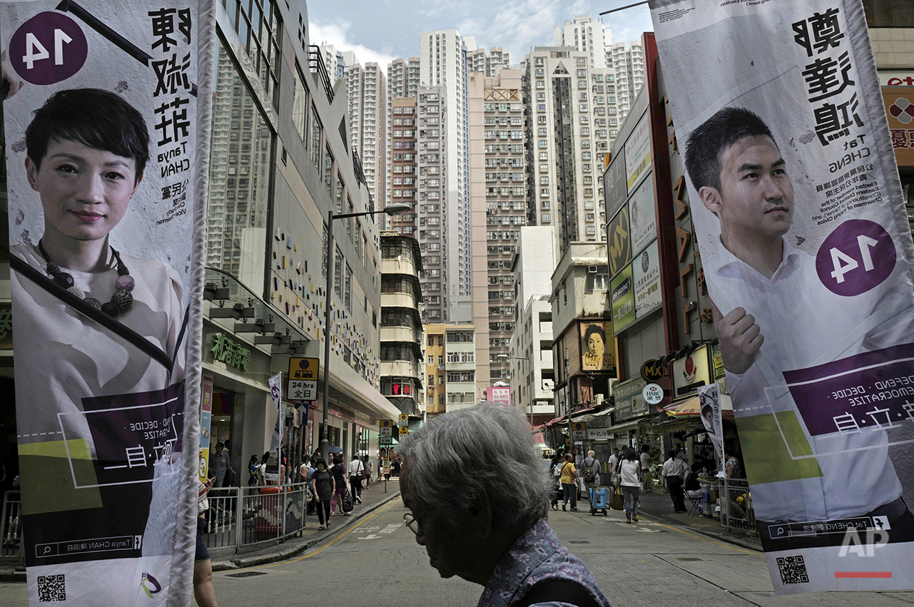 In this Aug. 27, 2016 photo, a woman walks past Hong Kong election banners for pro-democracy candidates Tanya Chan, left, and Cheng Tat-hung of the Civic Party in Hong Kong. Hong Kongers head to the polls Sunday, Sept. 4, 2016 to choose candidates for the semiautonomous city's legislature, in the first major election since 2014's pro-democracy street protests. That movement drew world attention to the former British colony's struggle over stunted democratic development under Chinese rule and paved the way for a burgeoning independence movement that's complicating the upcoming vote. (AP Photo/Vincent Yu)