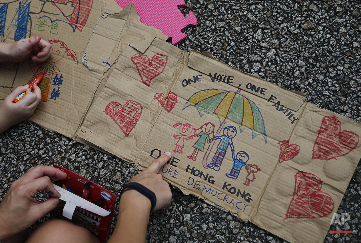 "A mother and daughter draw pictures to symbolise their hopes for democracy, Thursday, Oct. 2, 2014 in Hong Kong.  China's ruling party mouthpiece warned of ""chaos"" and expressed strong support for Hong Kong's embattled leader in his face-off with pro-democracy protesters who have threatened to occupy government offices unless he steps down by the end of Thursday. (AP Photo/Wong Maye-E)"