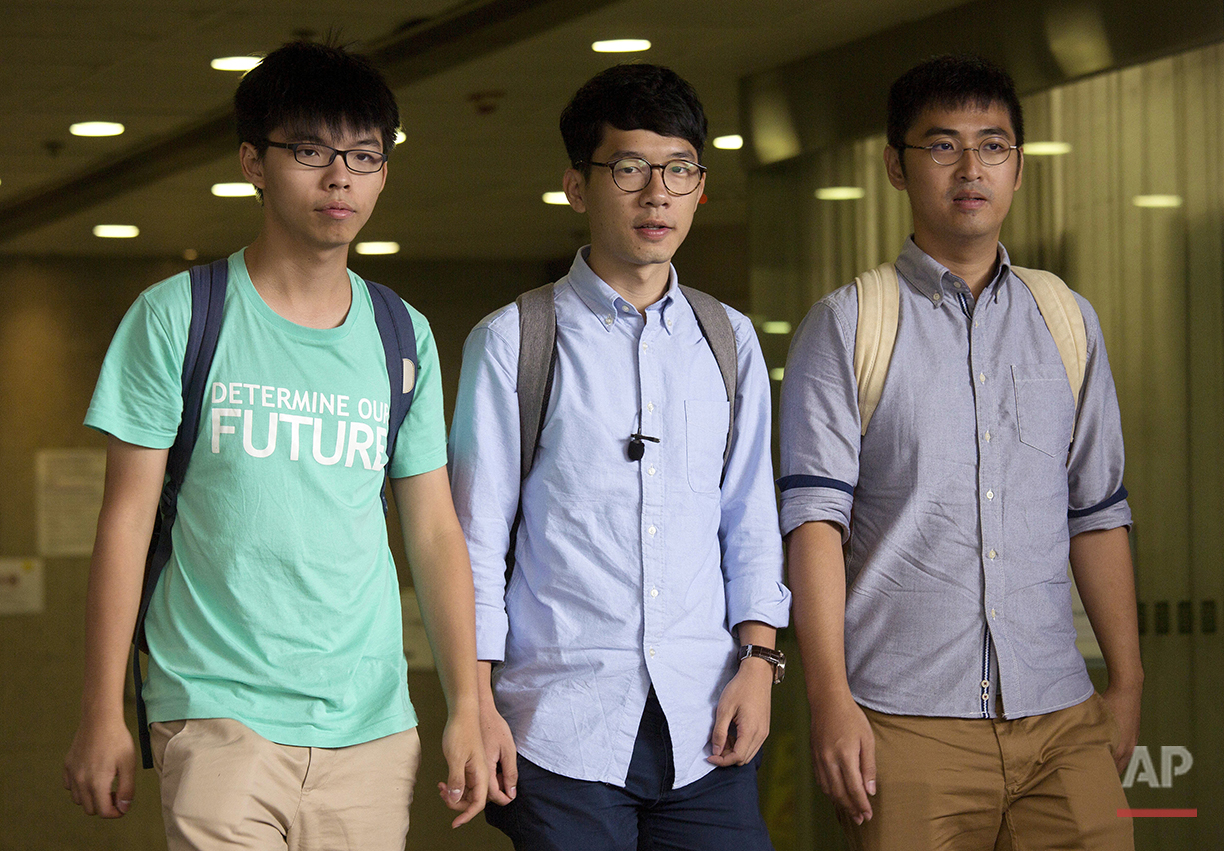 Three Hong Kong student protest leaders, from left, Joshua Wong, Nathan Law and Alex Chow walk out from a magistrate's court in Hong Kong, Aug. 15, 2016.  (AP Photo/Vincent Yu)